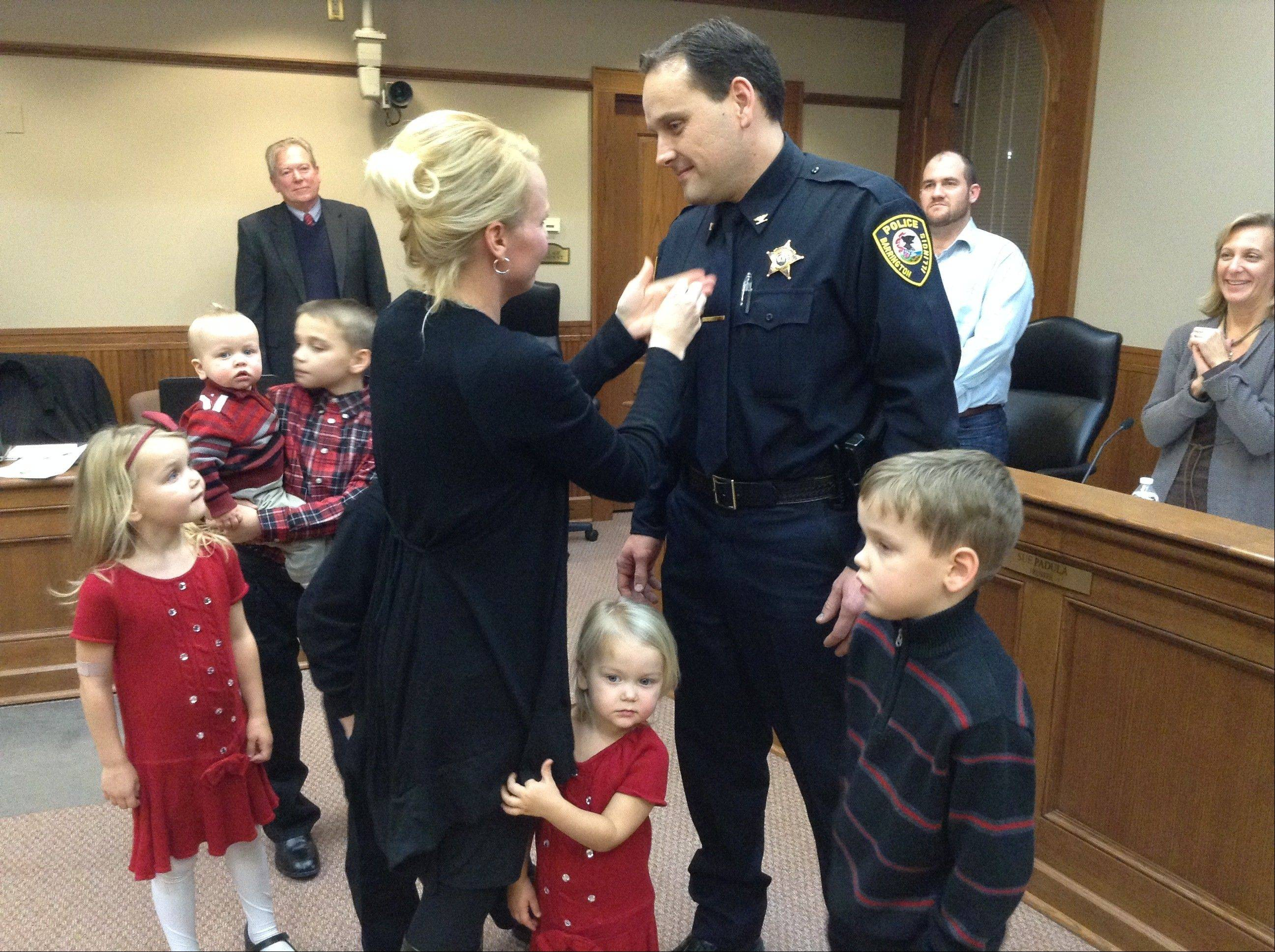 Barrington's new police chief, David Dorn, is pinned with his new rank by his wife Jennifer as their children and the Barrington village board looks on Monday night. Dorn, a 15-year department veteran, replaces former chief Jerry Libit, who retired in May.