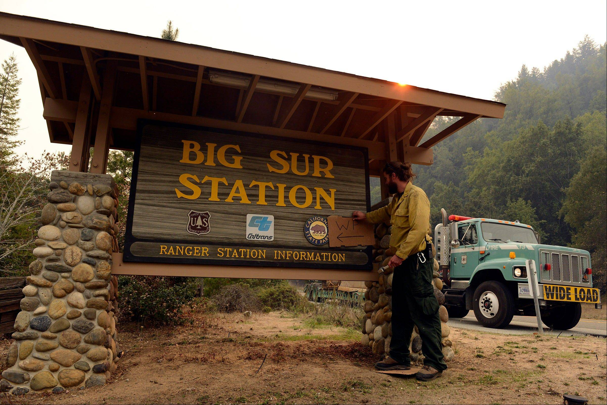 U.S. Fire Service firefighter Andrew Way puts a sign up at the Big Sur Station indicating the area as a water point for other firefighters as they battle a wildland fire in the Pfeiffer Ridge area in Big Sur, Calif. on Monday Dec. 16, 2013.