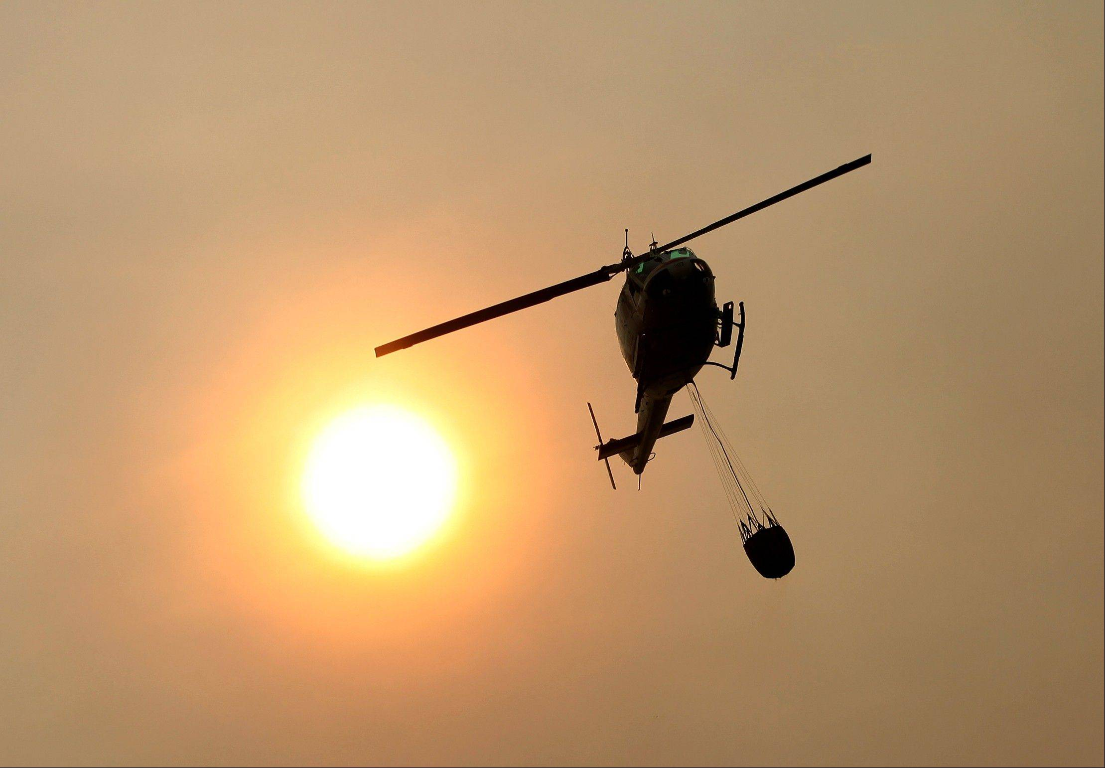 A Cal Fire helicopter flies over Pfeiffer Ridge on Monday, Dec. 16, 2013, in Big Sur, Calif. The wildfire burning Monday in the Big Sur area of California destroyed at least 15 homes and forced about 100 people to evacuate as it chewed through dry vegetation on its way toward the ocean.