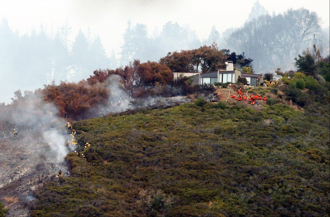 Fire crews work to contain the fire atop Pfeiffer Ridge, Monday, Dec. 16, 2013, in Big Sur, Calif. The wildfire burning Monday in the Big Sur area of California destroyed at least 15 homes and forced about 100 people to evacuate as it chewed through dry vegetation on its way toward the ocean. (