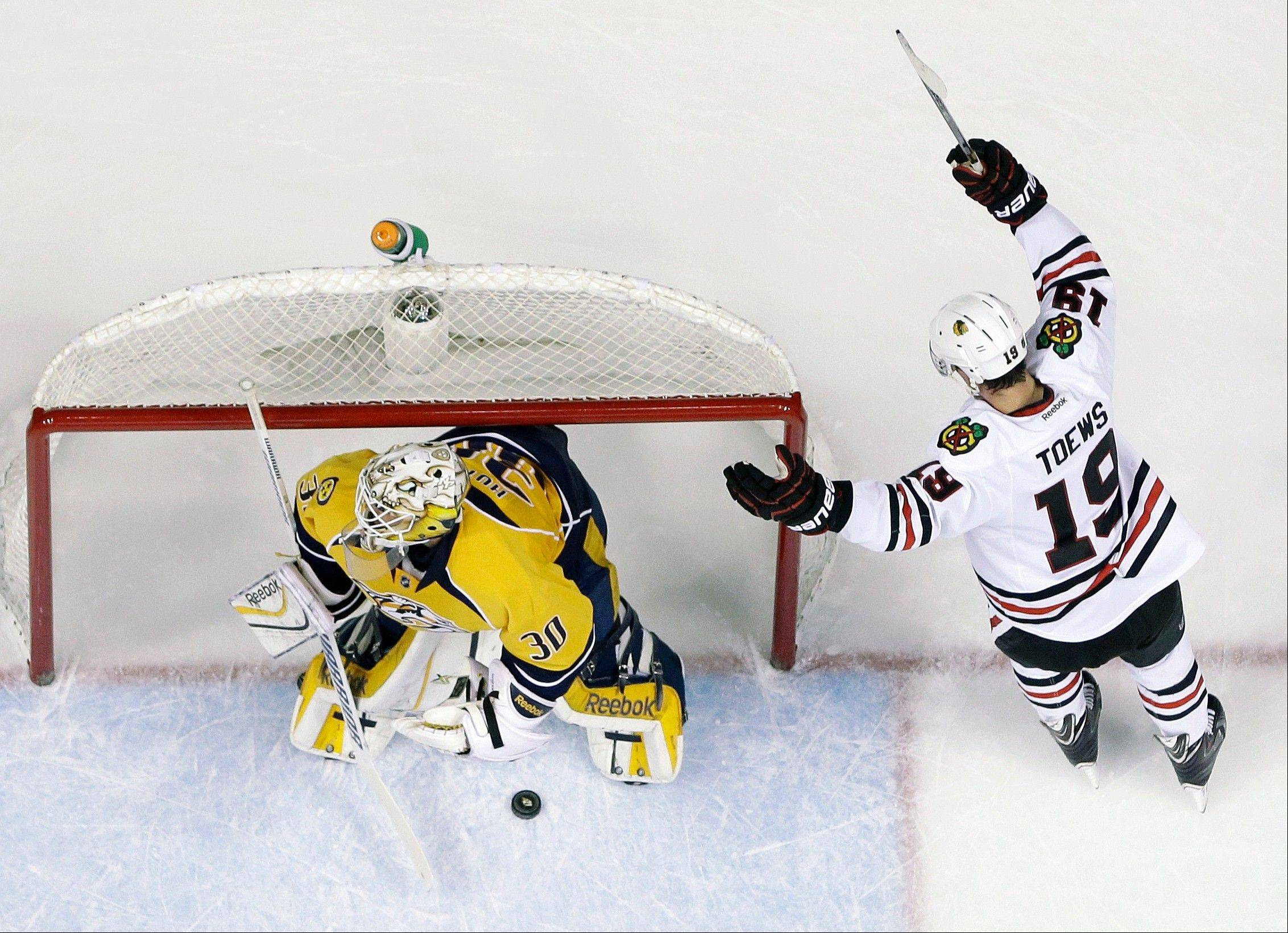 Jonathan Toews celebrates a goal by Blackhawks teammate Patrick Kane against Predators goalie Carter Hutton in the first period Tuesday night.