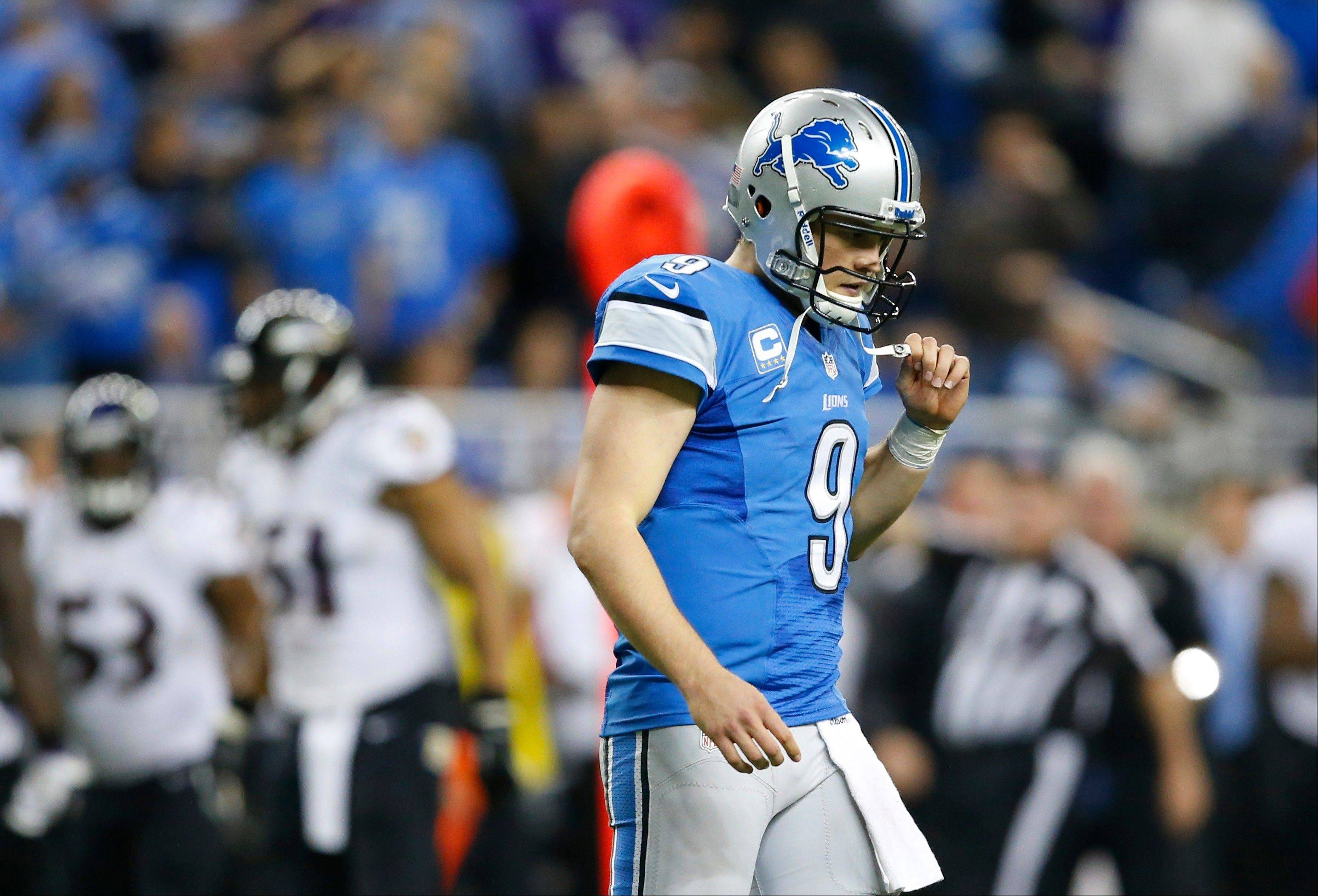 Detroit Lions quarterback Matthew Stafford walks off the field after Baltimore Ravens free safety Matt Elam intercepted his pass with less than a minute to play Monday night. Detroit's loss gave control of the division to the first-place Bears with two games to play.