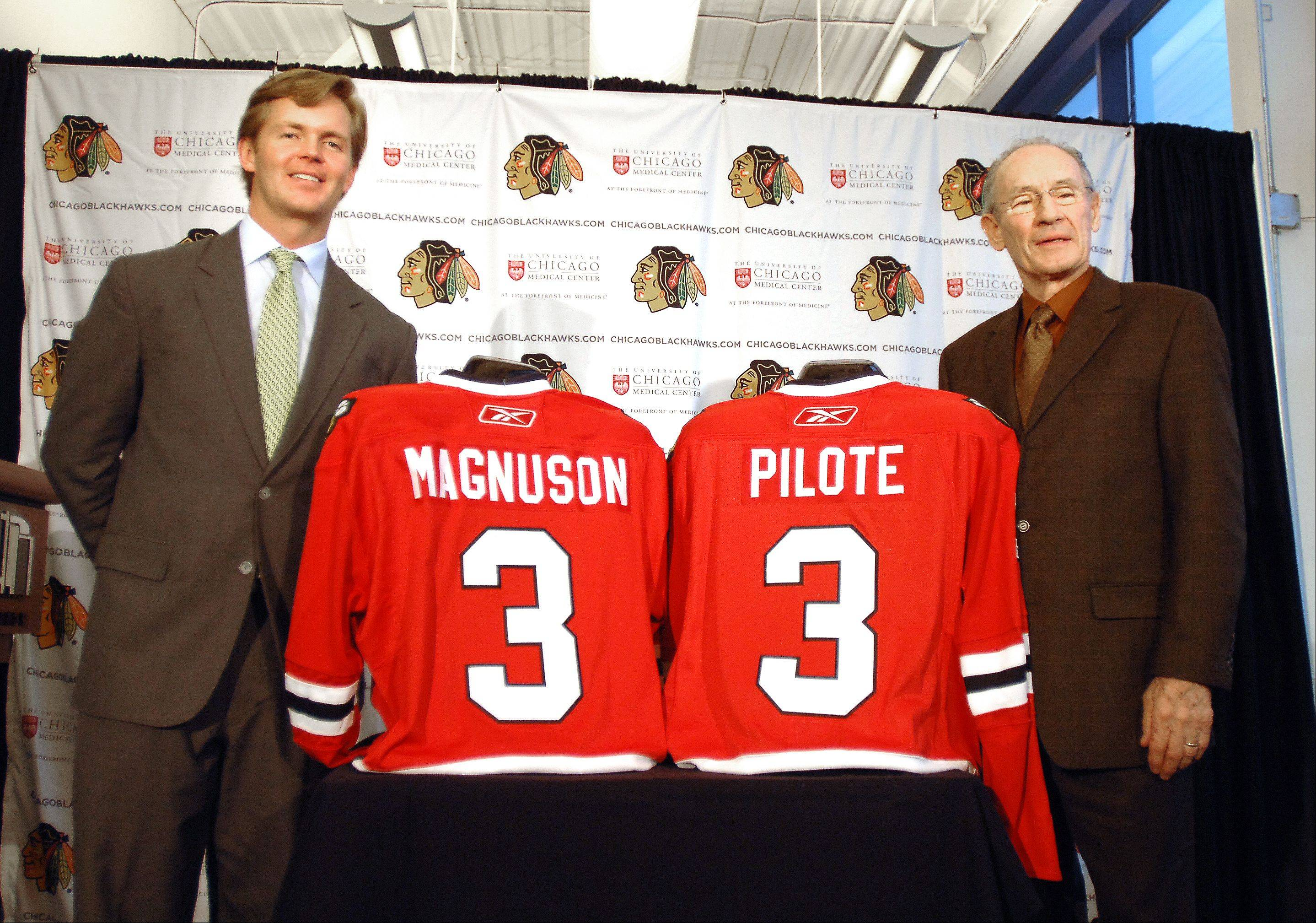 Kevin Magnuson, the son of late Keith Magnuson, and former Hawks captain Pierre Pilote pose with the retired No. 3 jerseys.