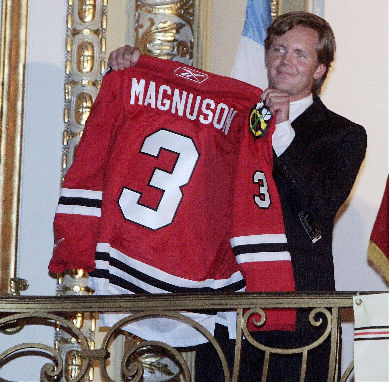 Kevin Magnuson holds up the jersey of his father, Keith Magnuson.