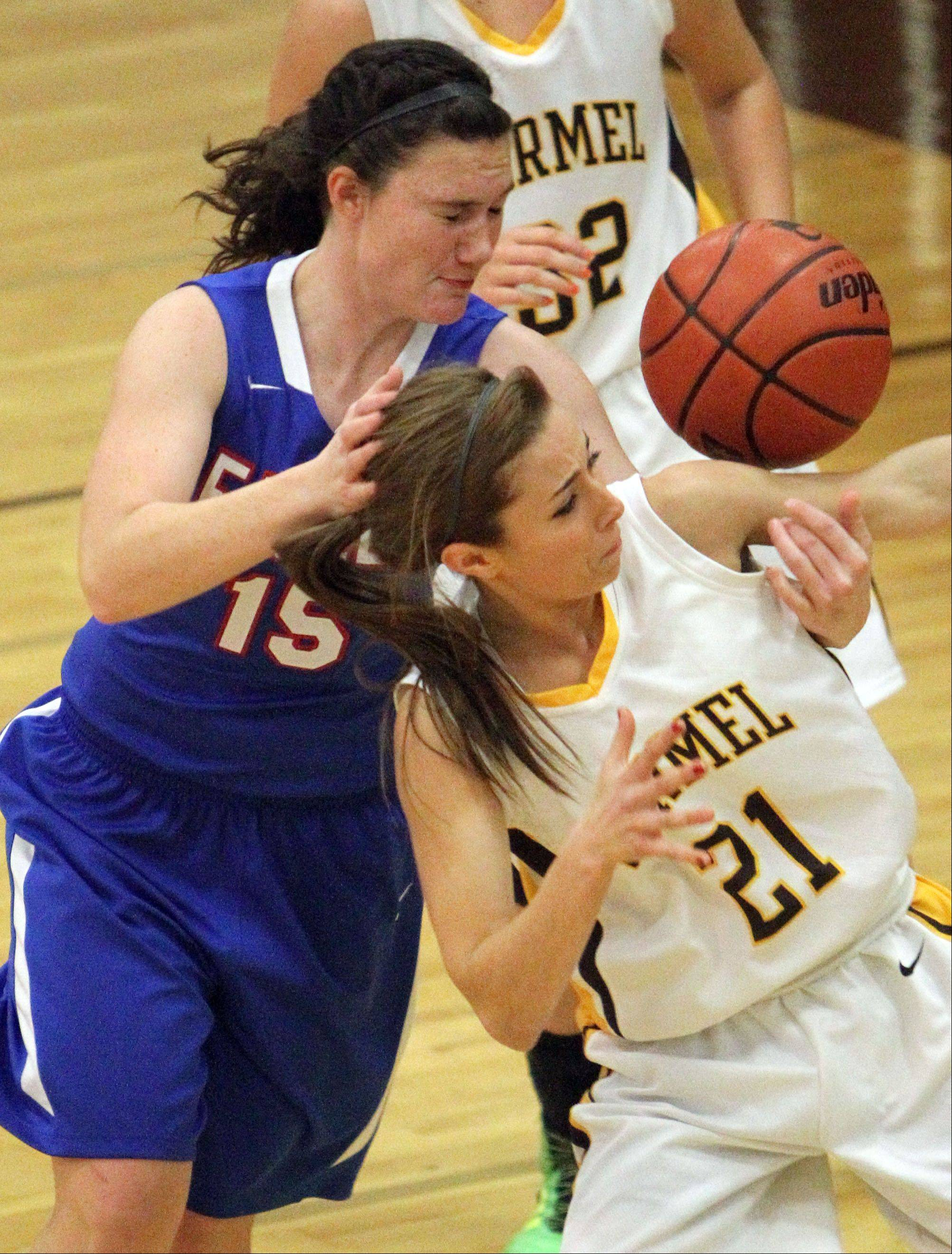 Lakes' Nicole Denman, left, and Carmel's Nicole Bitter eye the loose ball during Monday's basketball game in Mundelein.