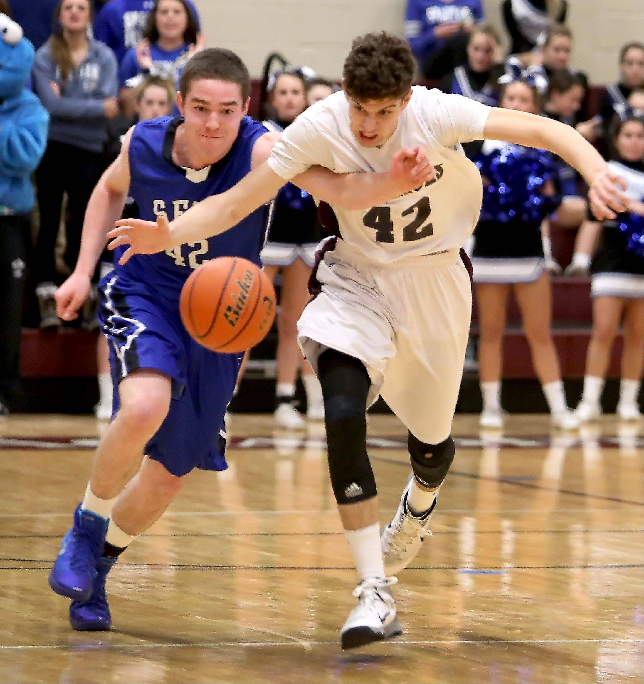 St. Francis's Kilian Brown, left, and Wheaton Academy's Chandler Fuzak chase down a loose ball during Tuesday's basketball game in West Chicago.