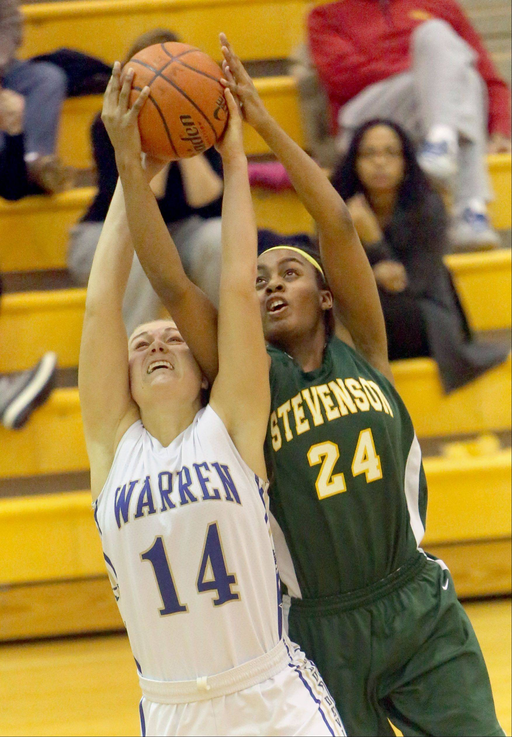 Warren's Kristen O'Brien (14) and Stevenson's Taylor Buford pull down a rebound during Tuesday's basketball game in Gurnee.