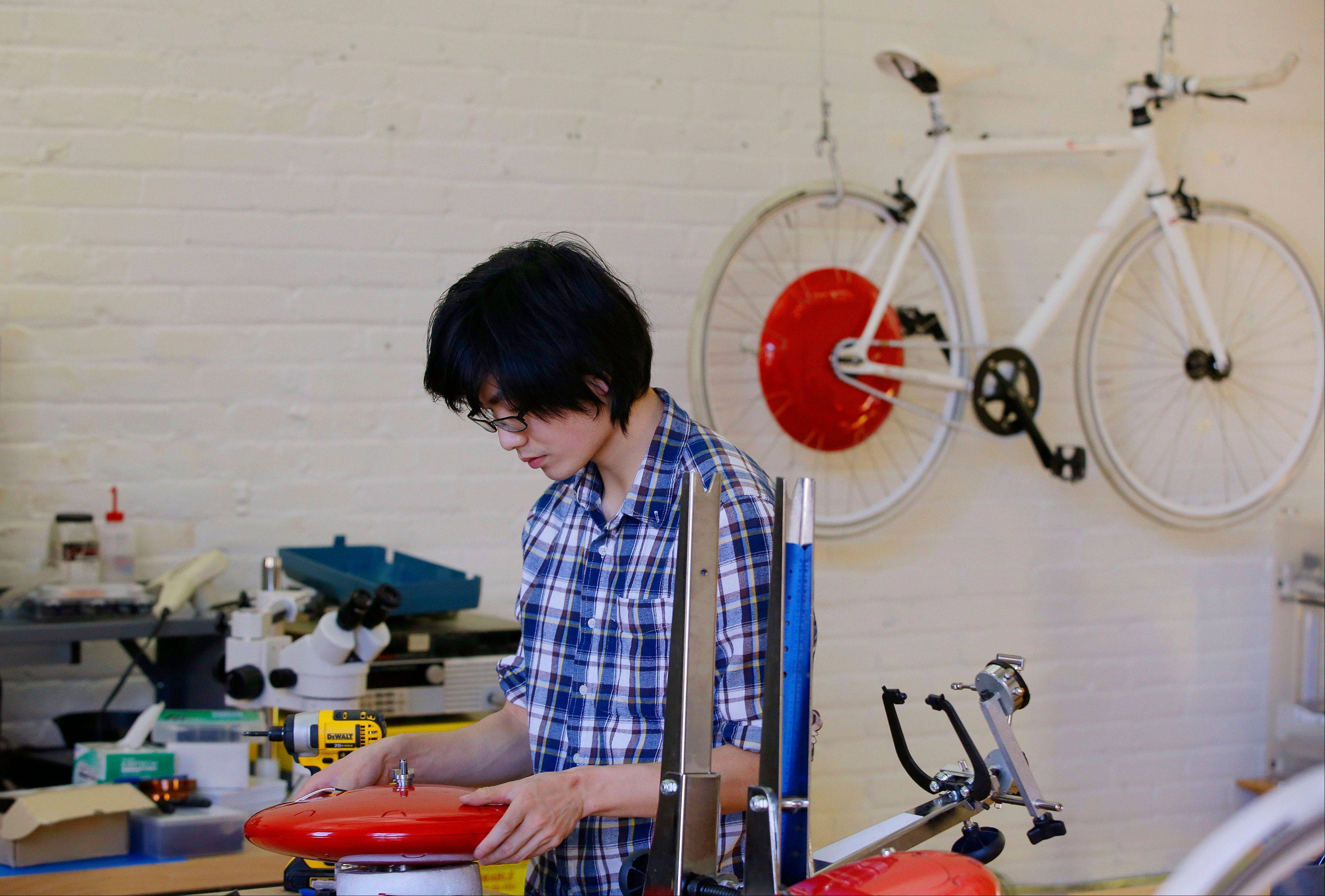 Mechanical and software engineer Julian Fong works on a development to the Copenhagen Wheel, the red disk, a human/electric hybrid bicycle engine, at Superpedestrian in Cambridge, Mass.