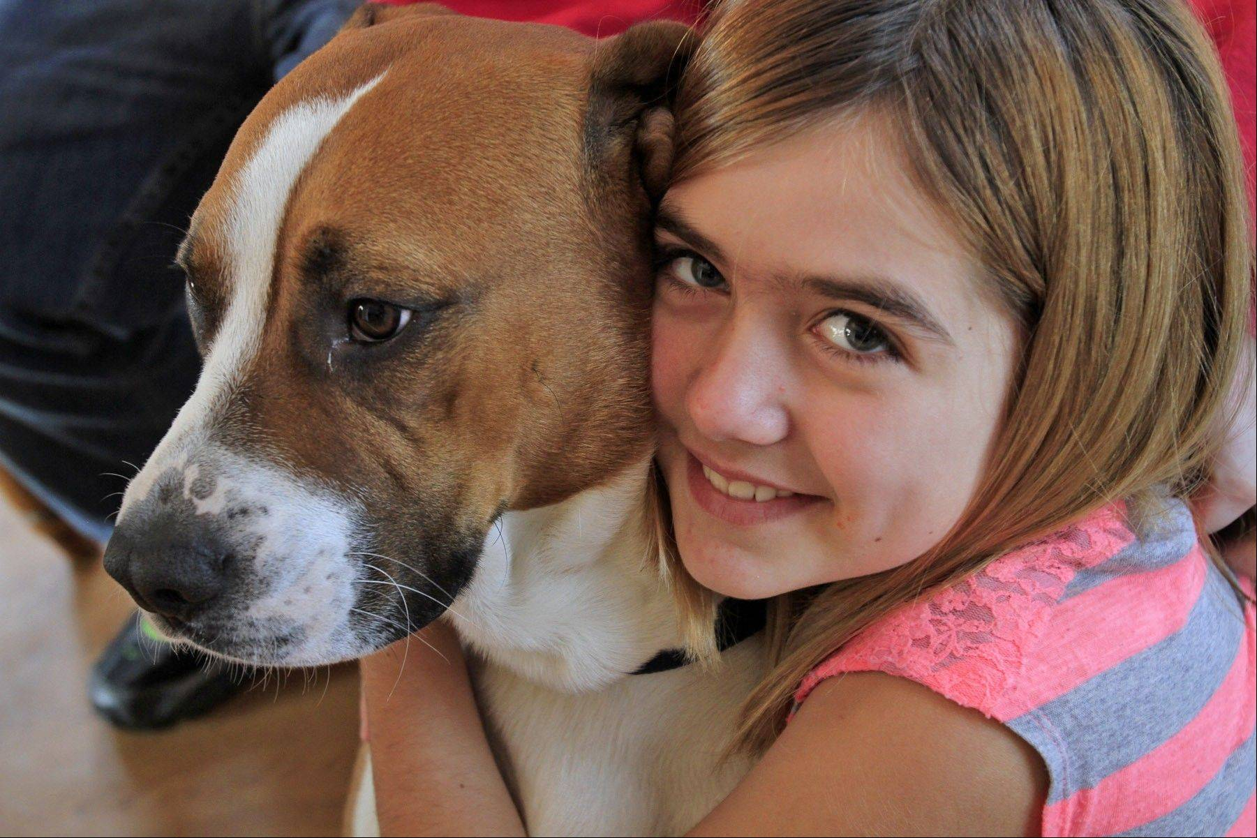 Rosco poses with his family, getting a hug from Madison Pritchard, 10, in their Mellott, Ind., home on Wednesday. He had been lost during a recent tornado.