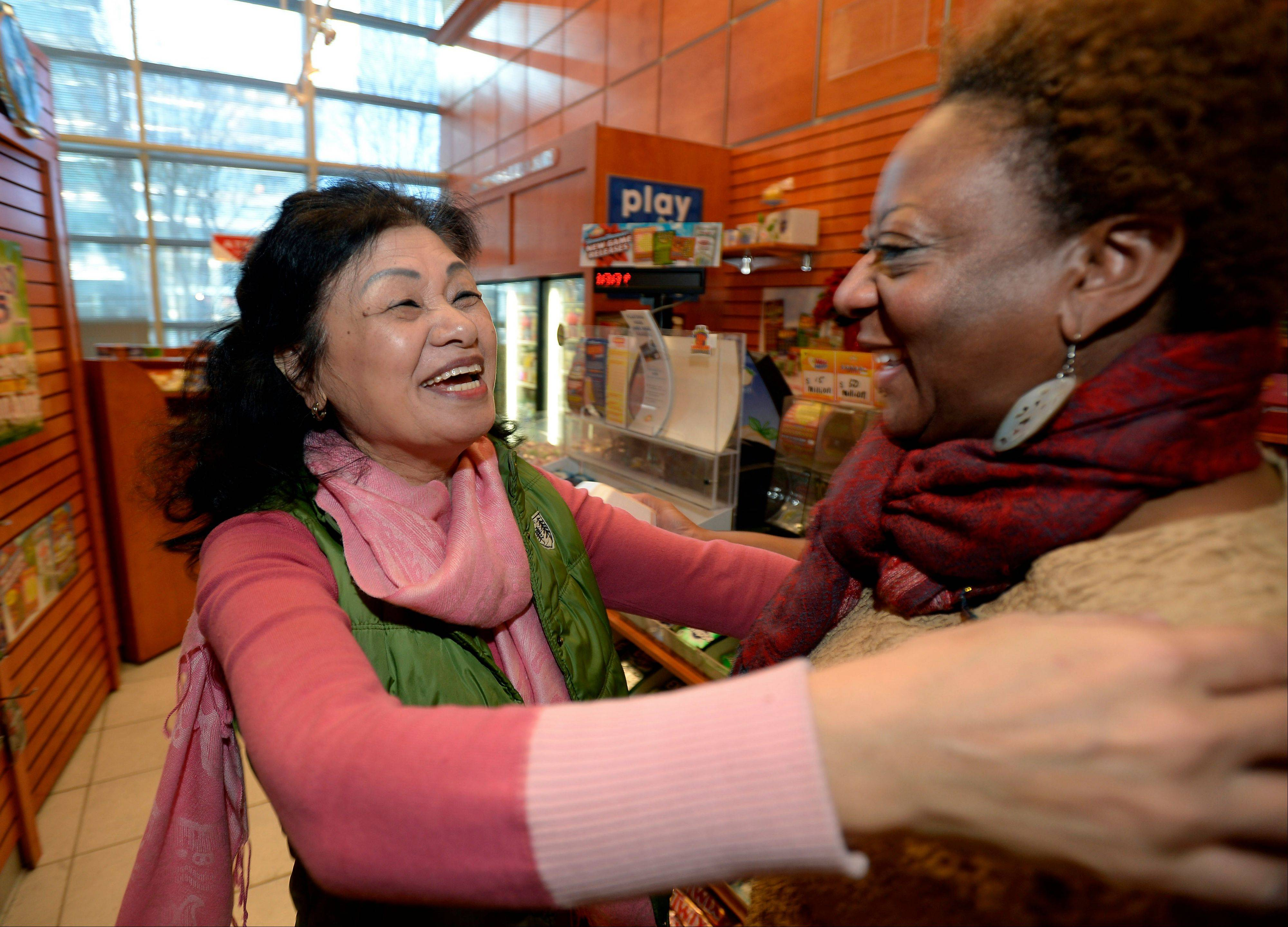 Owner Young Soolee, left, is congratulated by regular customer Dawn Palmerat her small Alliance Center office bulding newsstand on Wednesday in Atlanta after lottery officials said one of two winning Mega Millions lottery tickets were purchased from her store in Tuesday�s $636 million drawing. The store owner said she sold 1,300 lottery tickets on Tuesday rather than the normal sales of about 100 tickets.