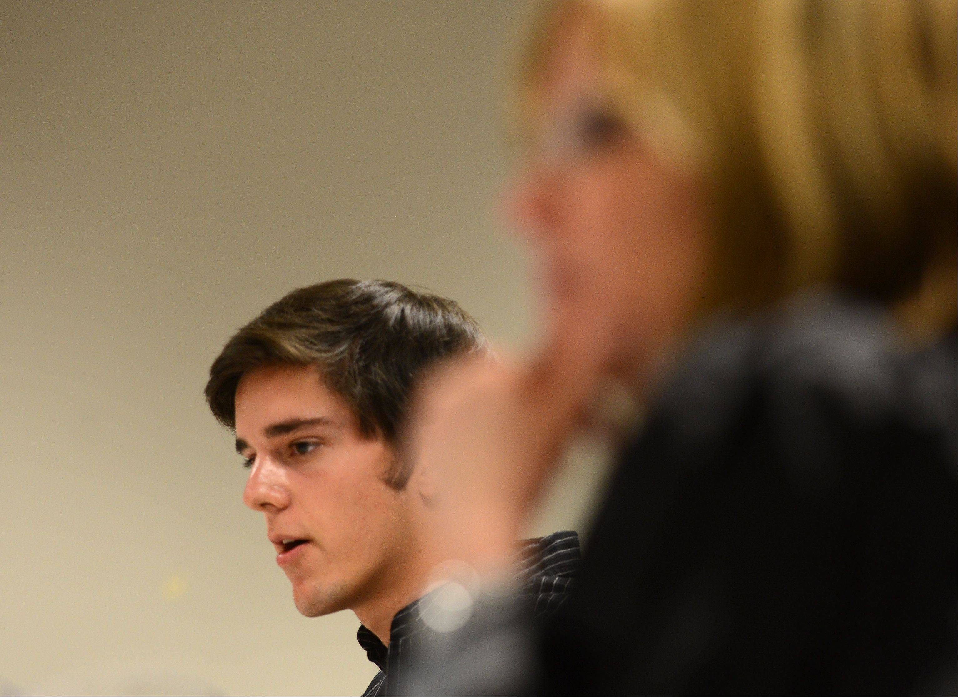 David Comperda offers his testimony as the plaintiff as students at Geneva High School conduct a mock trial Tuesday for a car crash lawsuit that might have involved alcohol. Local attorney and former Kane County prosecutor, Kim Klein, right, acted as judge.