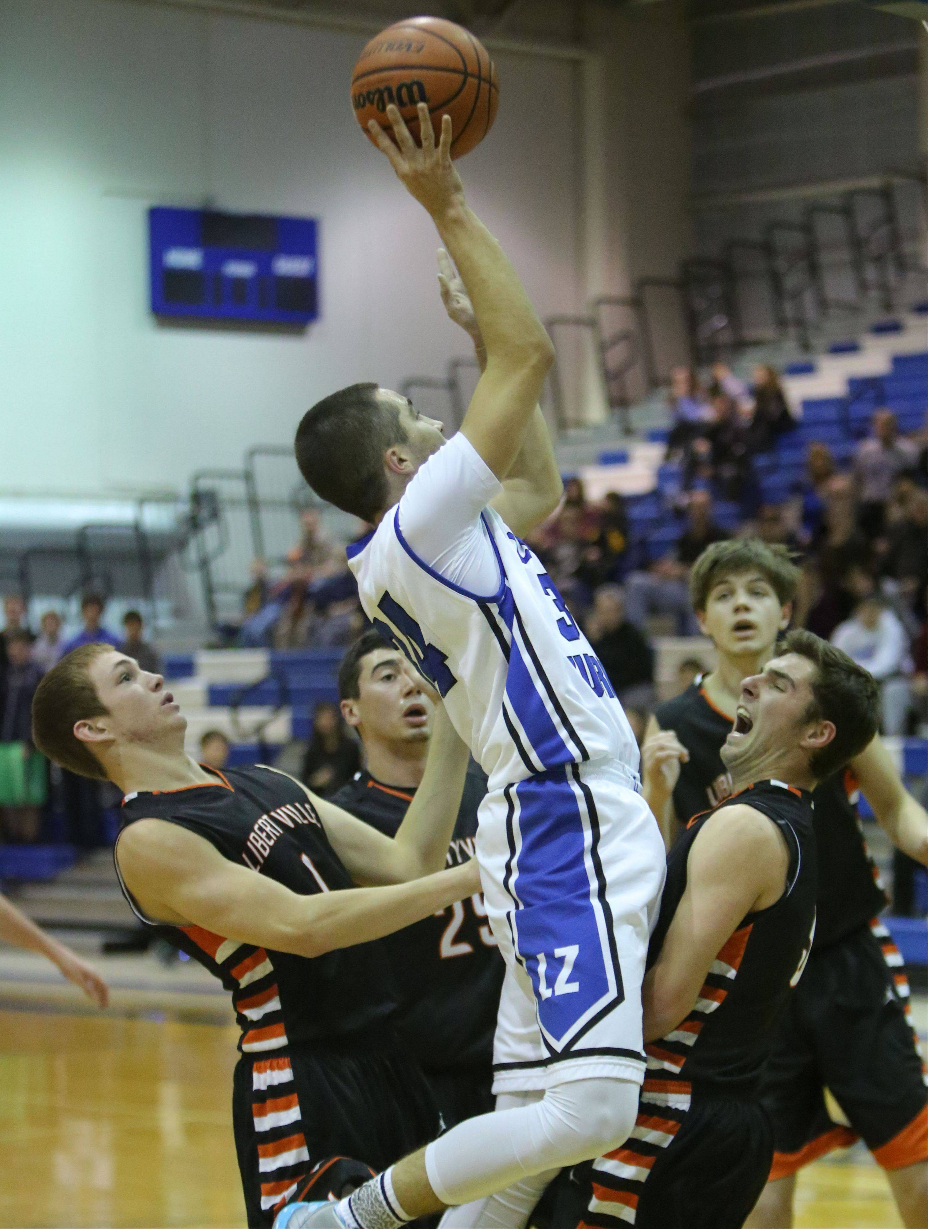 Lake Zurich's Mike Travlos, middle, drives on Libertyville's, from left, Brian Scanlan, Johnny Vernasco and Matt Reed on Wednesday night at Lake Zurich High School.