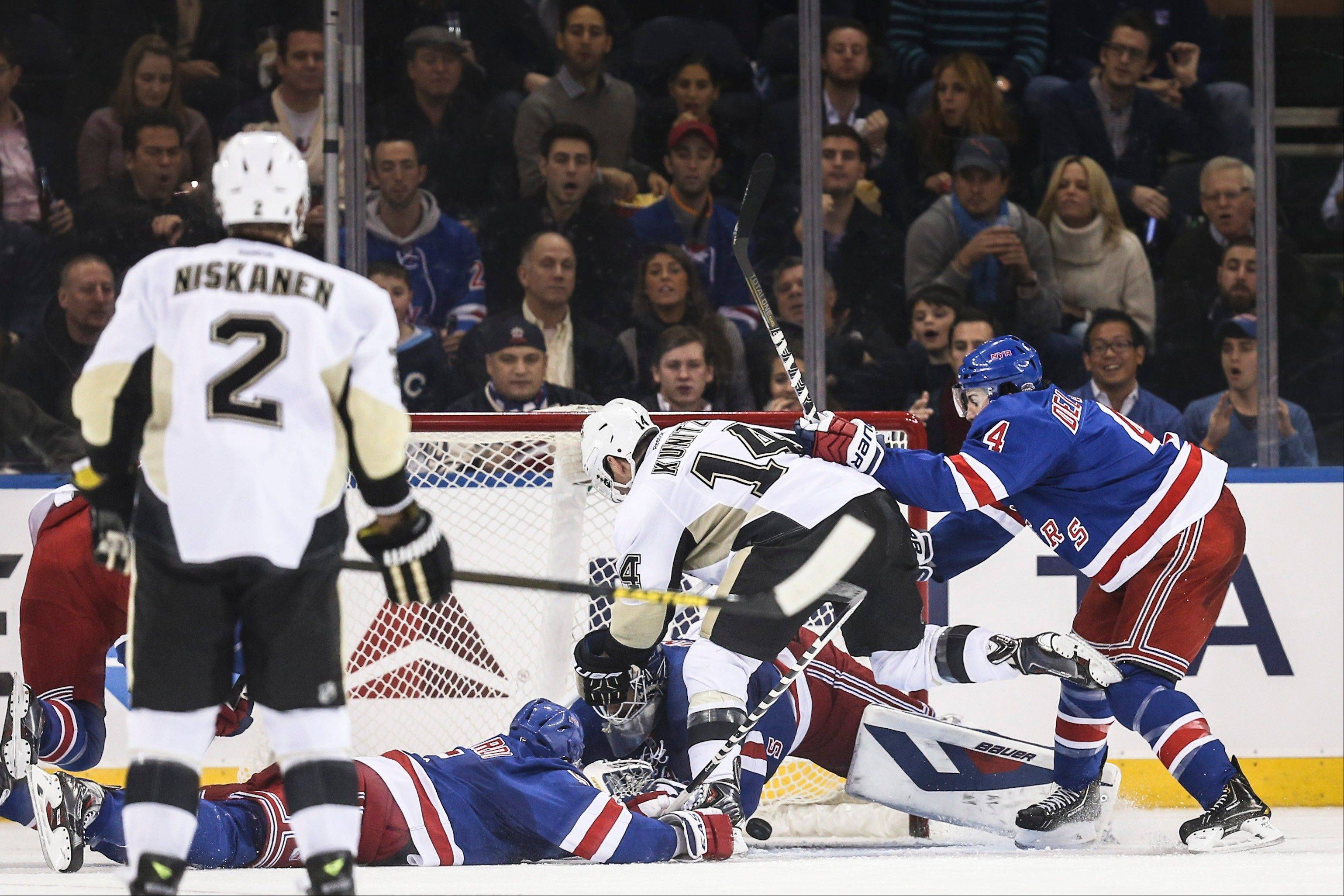 Pittsburgh Penguins left wing Chris Kunitz (14) scores against New York Rangers goalie Henrik Lundqvist (30) through Rangers defensemen Dan Girardi (5) and Michael Del Zotto (4) during the second period of their NHL hockey game on Wednesday in New York.
