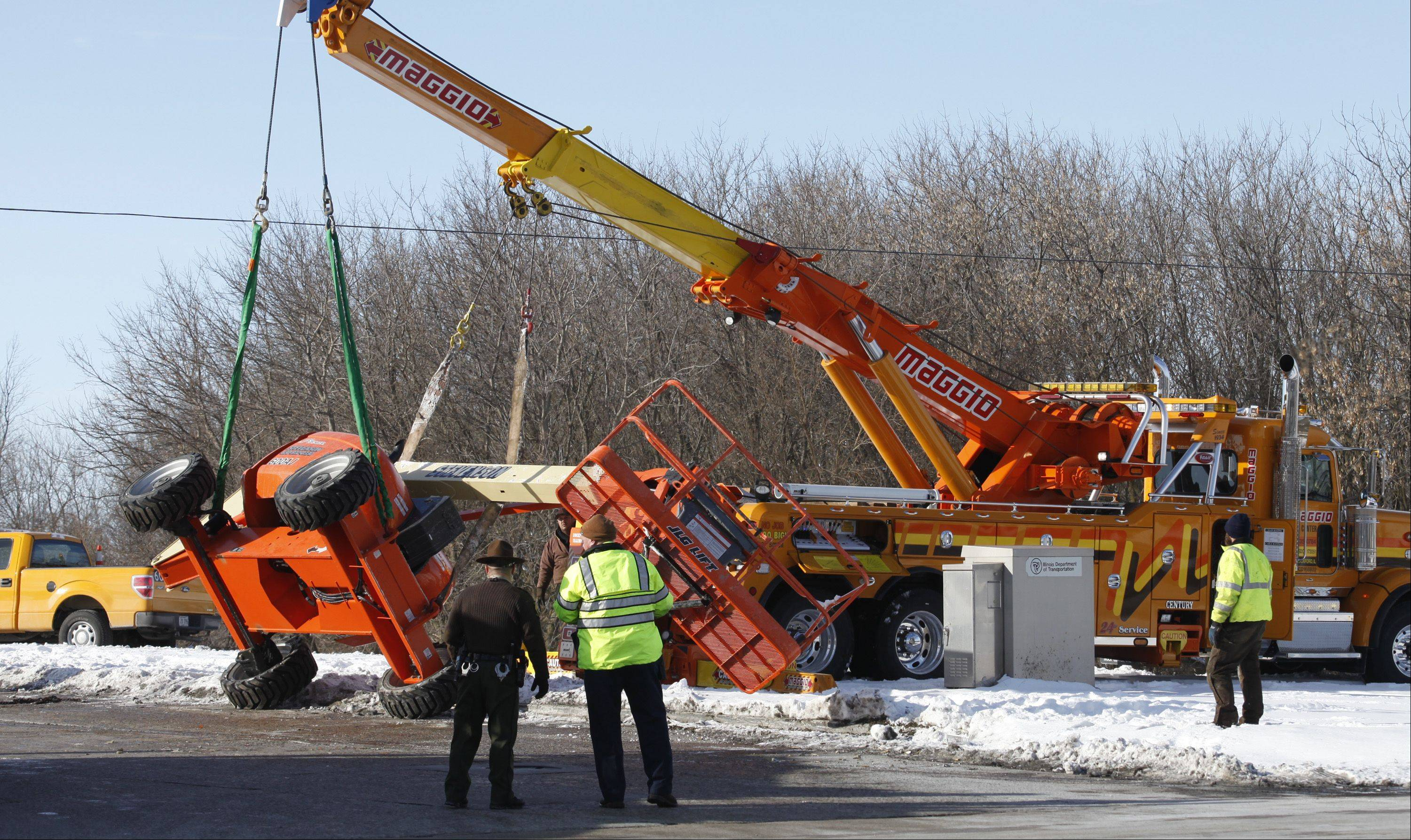 A boom lift is lowered onto its wheels Wednesday after it fell from a truck at the intersection of Route 20 and the Jane Addams Tollway entrance ramp in Hampshire. Traffic access to the tollway was limited to vehicles coming from the west while the accident was cleared.