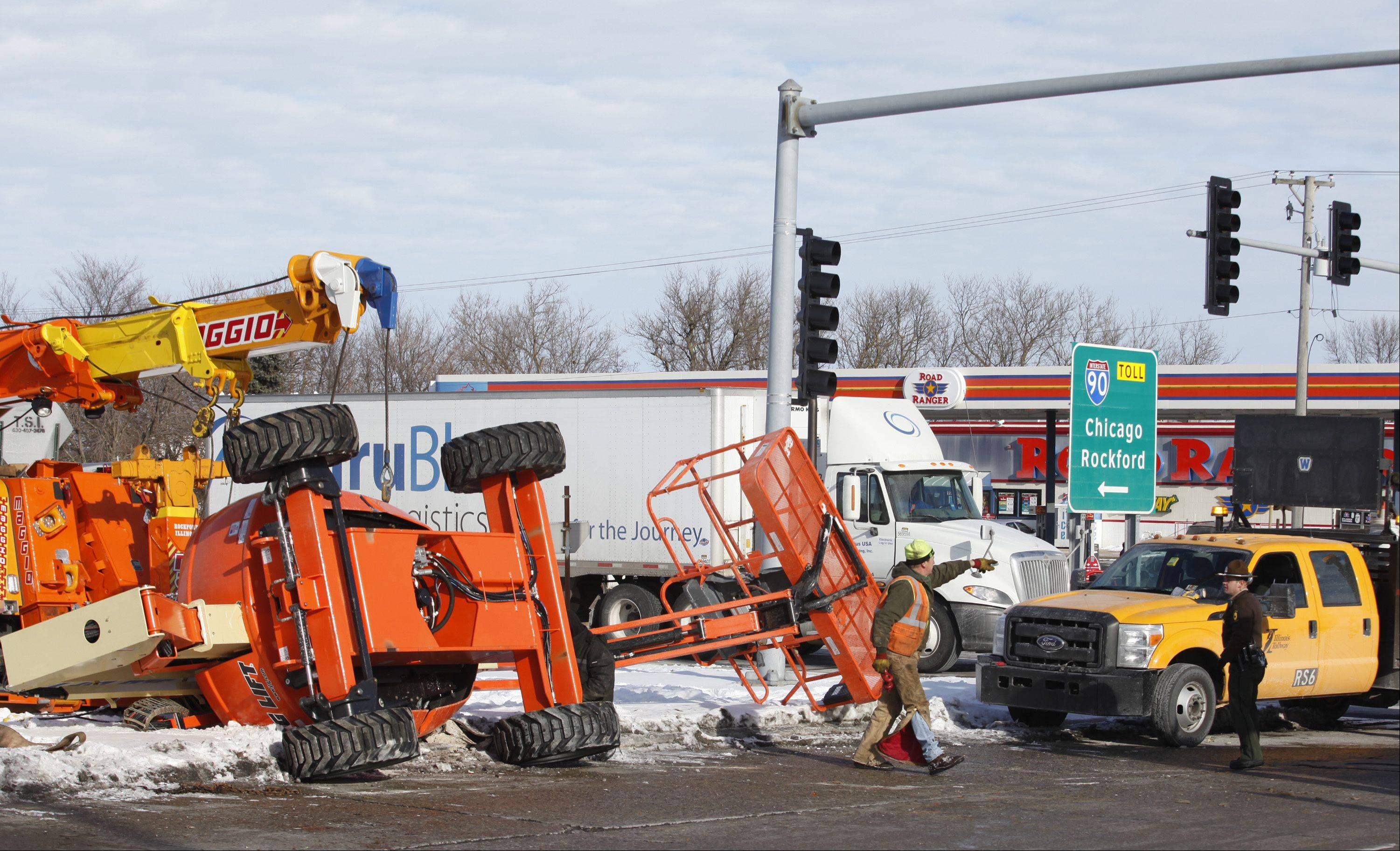 Towing crew members work to right a boom lift Wednesday morning after it fell from a truck at Route 20 and the Jane Addams Tollway entrance ramp in Hampshire. Traffic was snarled for awhile but the accident caused no injuries, police said.