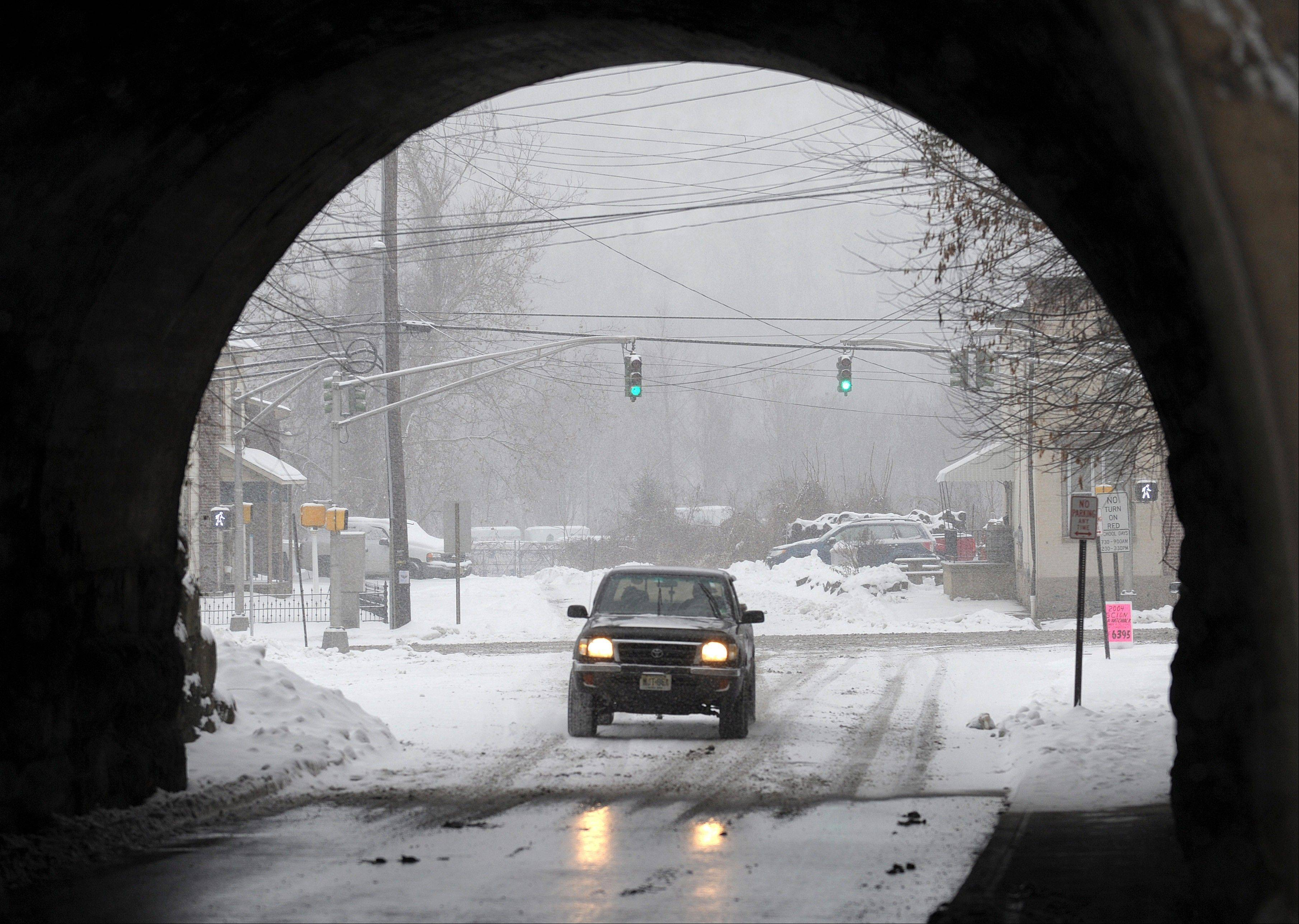 A truck drives through a tunnel on Center Street as snow falls on Tuesday, Dec. 17, 2013, in Phillipsburg, N.J.