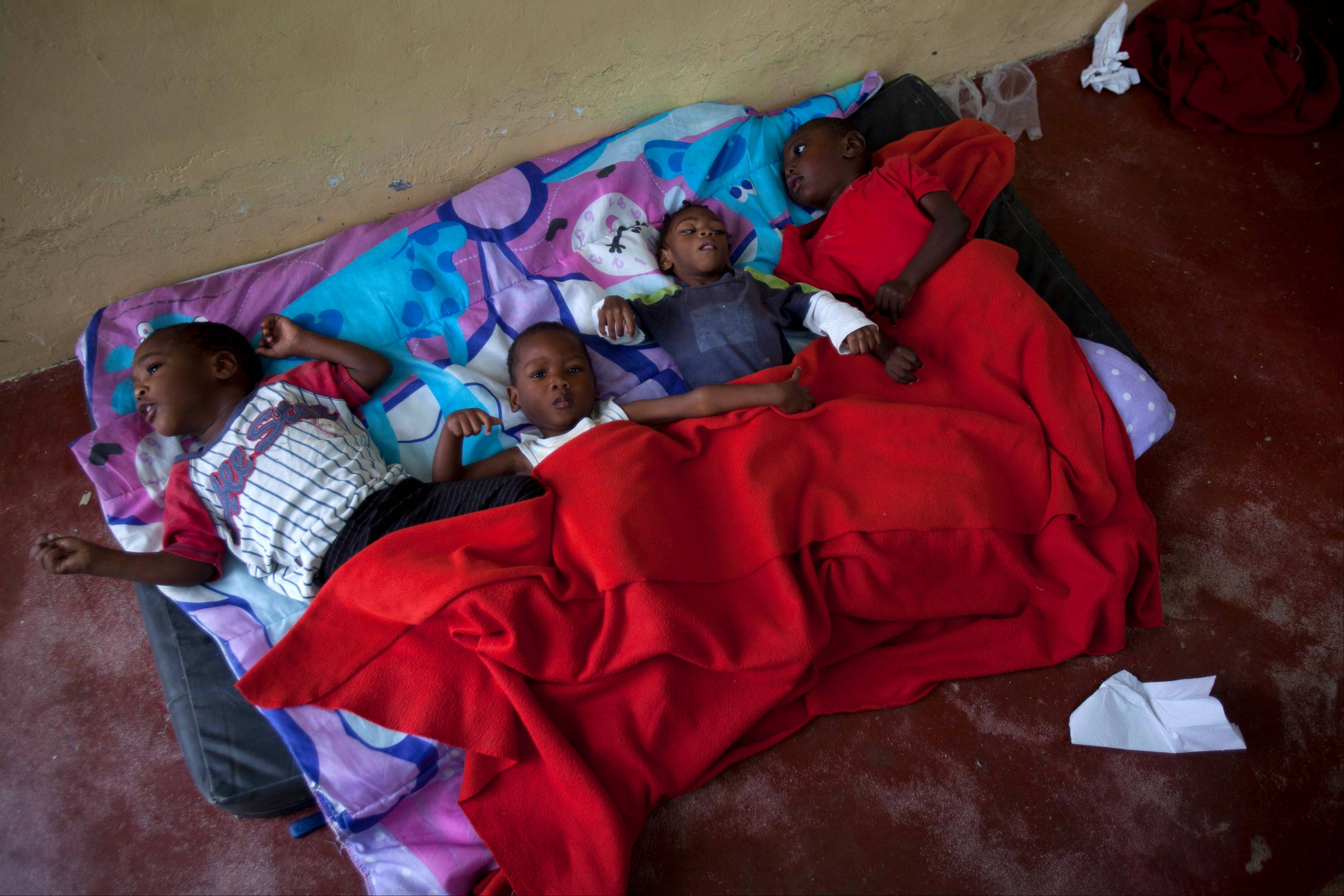 Children lay on a worn mattress placed on the floor of the U.S.-
