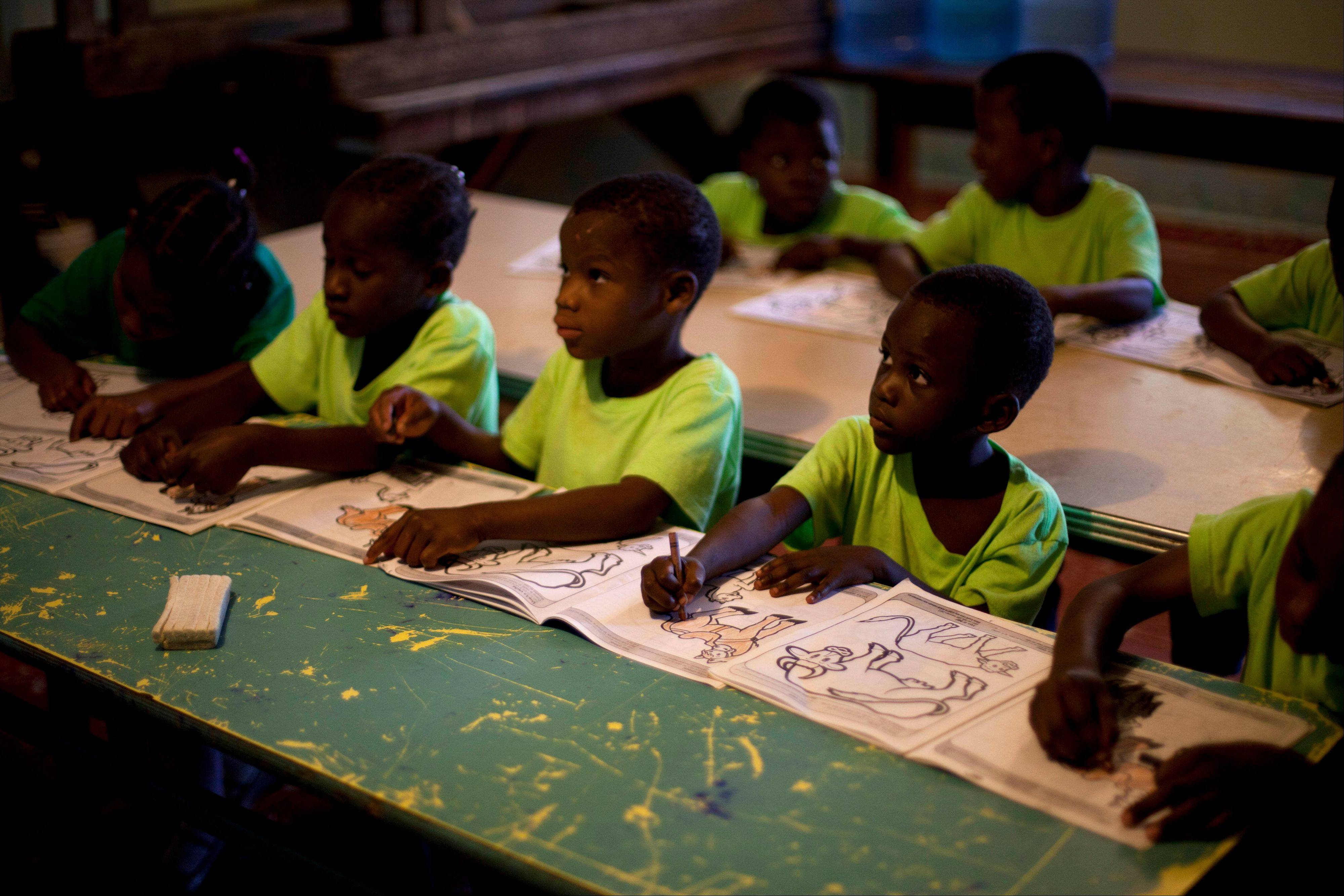 Children attend class in the U.S.-based Church of Bible Understanding orphanage in Kenscoff, Haiti. While many other orphanages also have failed Haiti's new national standards, the group's three-story building stands out because it's run by an organization with such an unusual, and successful fundraising operation.
