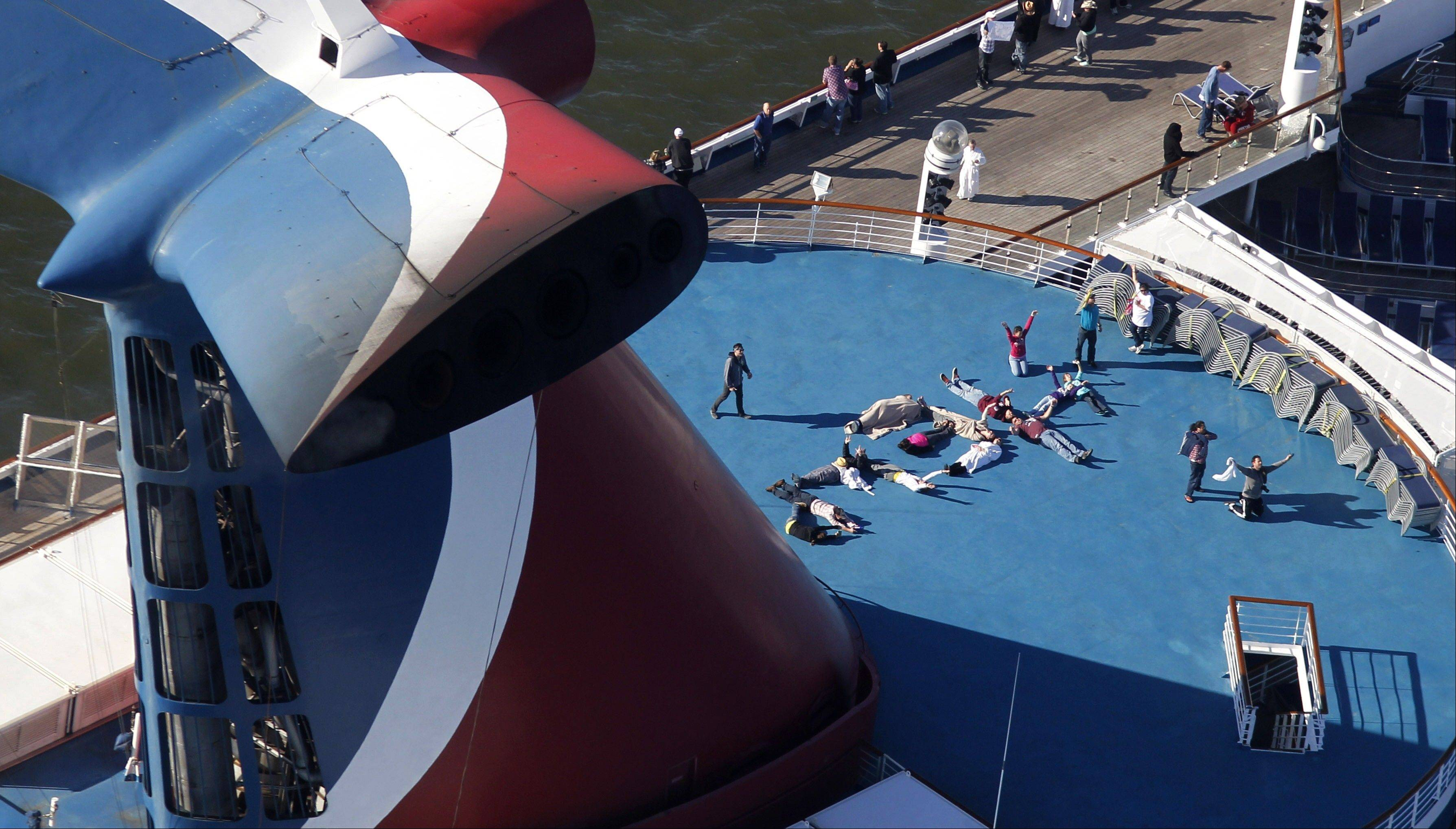 "Passengers spell out the word ""HELP"" aboard the disabled Carnival Lines cruise ship Triumph as it is towed to harbor off Mobile Bay, Ala. Carnival Cruise Lines knew about the risk of leaks from engine fuel hoses and recommended taking precautions on the ill-fated Carnival Triumph, which caught on fire at sea, according to documents filed in recent days."