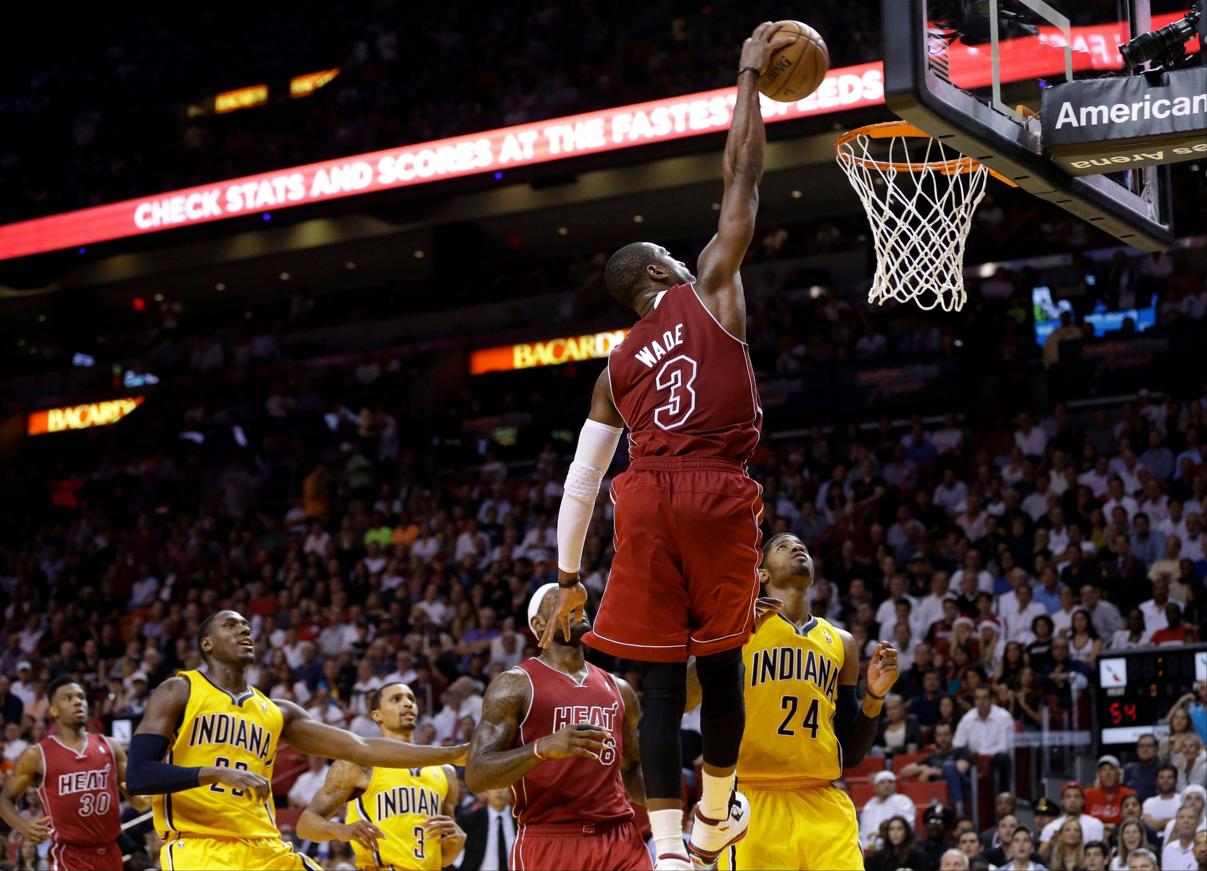 Miami Heat's Dwyane Wade (3) dunks over Indiana Pacers' Ian Mahinmi, left, and Paul George (24) during the second half of an NBA basketball game Wednesday in Miami. The Heat defeated the Pacers 97-94.
