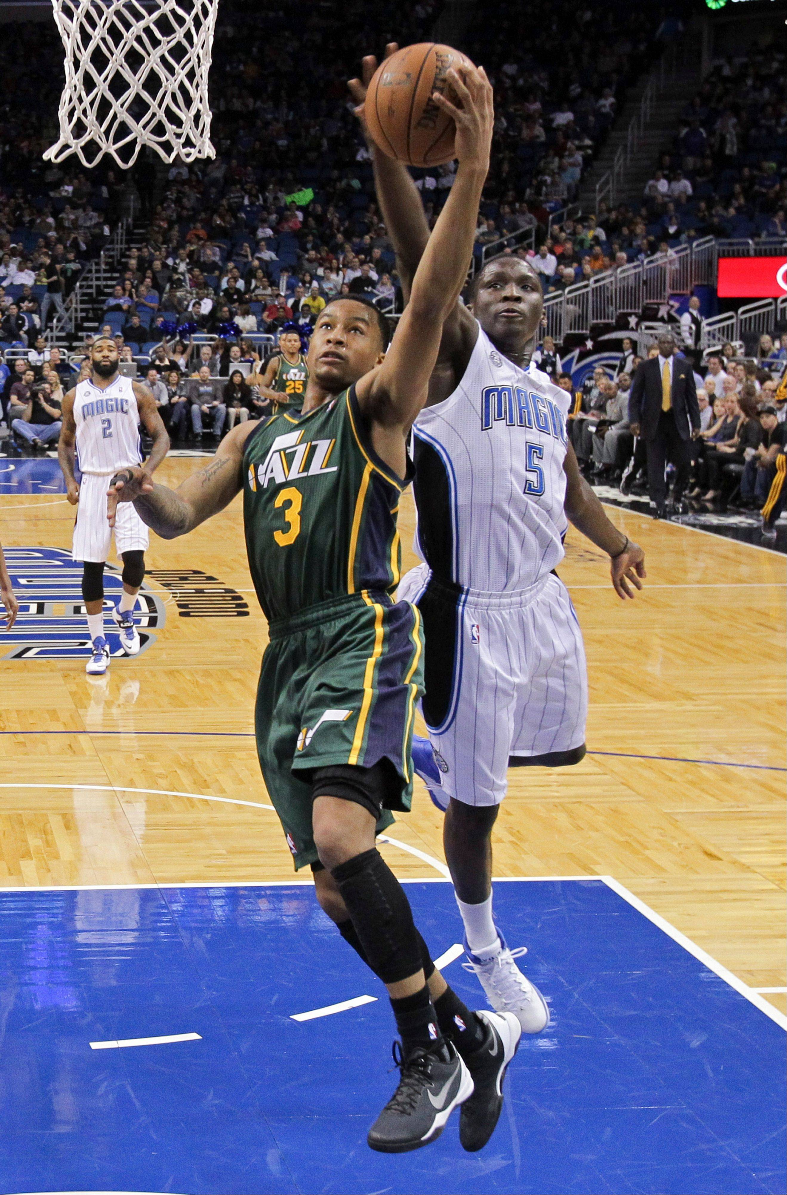 Orlando Magic's Victor Oladipo (5) blocks a shot by Utah Jazz's Trey Burke (3) during the first half of an NBA basketball game Wednesday in Orlando, Fla.