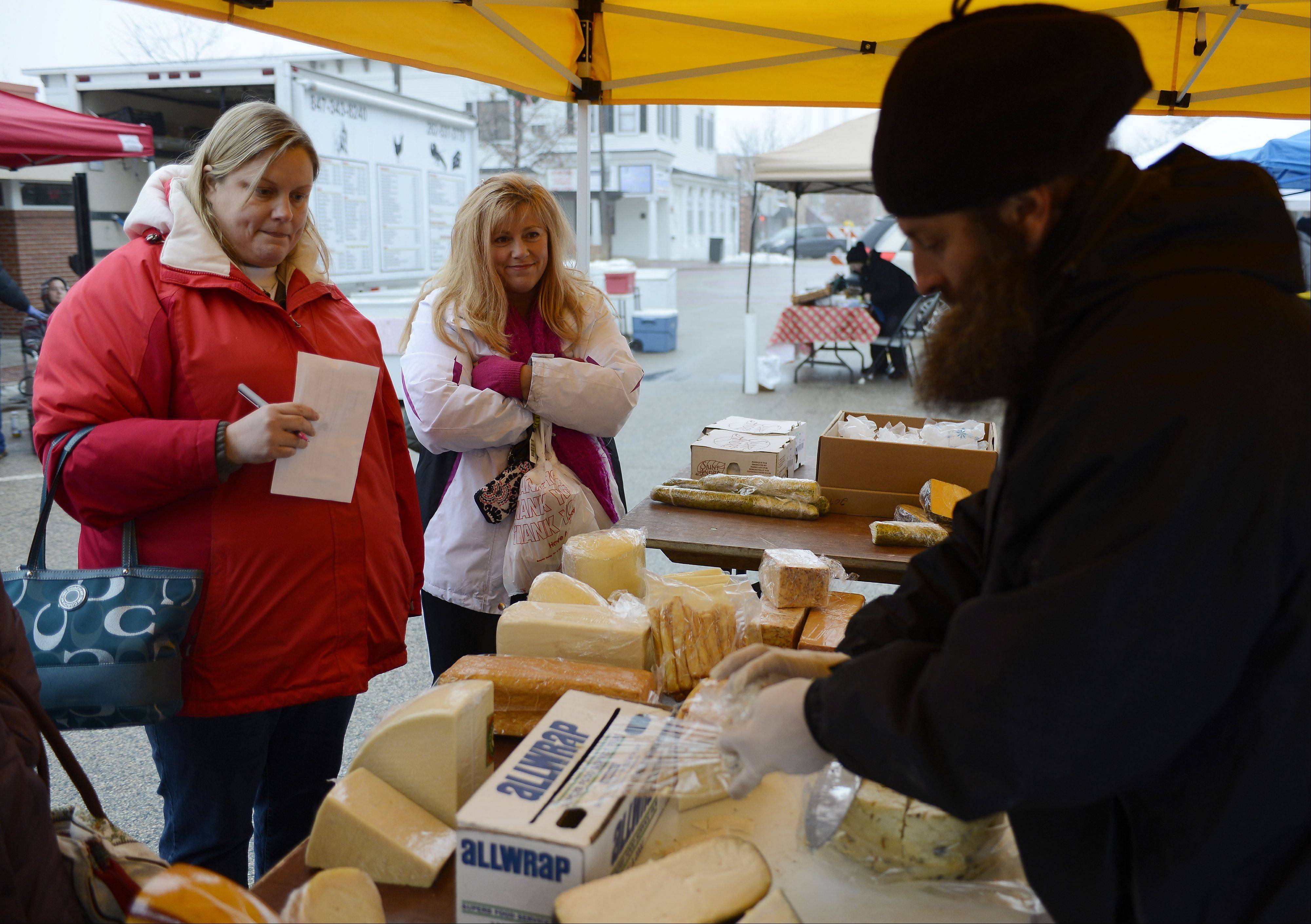 Jennifer Stiles, left, of Grayslake and Lori Maier of Gurnee wait as Michael Rhodes of the Cheese People wraps organic, handcrafted cheese during the Fall Farmers Market, the last of the season, Saturday in downtown Grayslake.