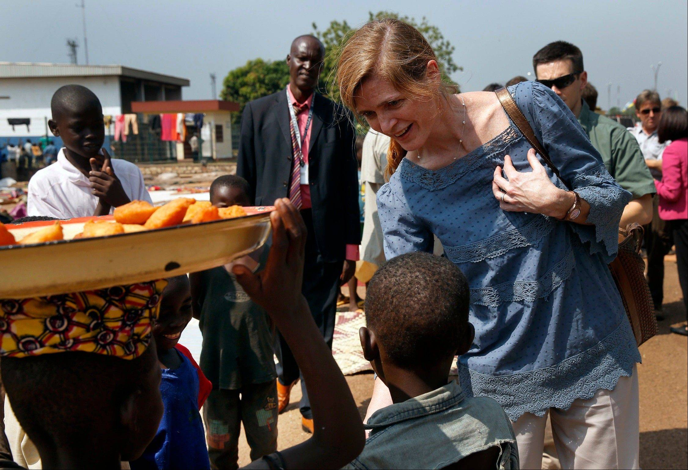 U.S. Ambassador to the United Nations Samantha Power greets IDP children at the makeshift camp where over 40,000 people found refuge at the airport in Bangui, Central African Republic, Thursday, Dec. 19, 2013. Power is on a one-day trip to the war stricken region.