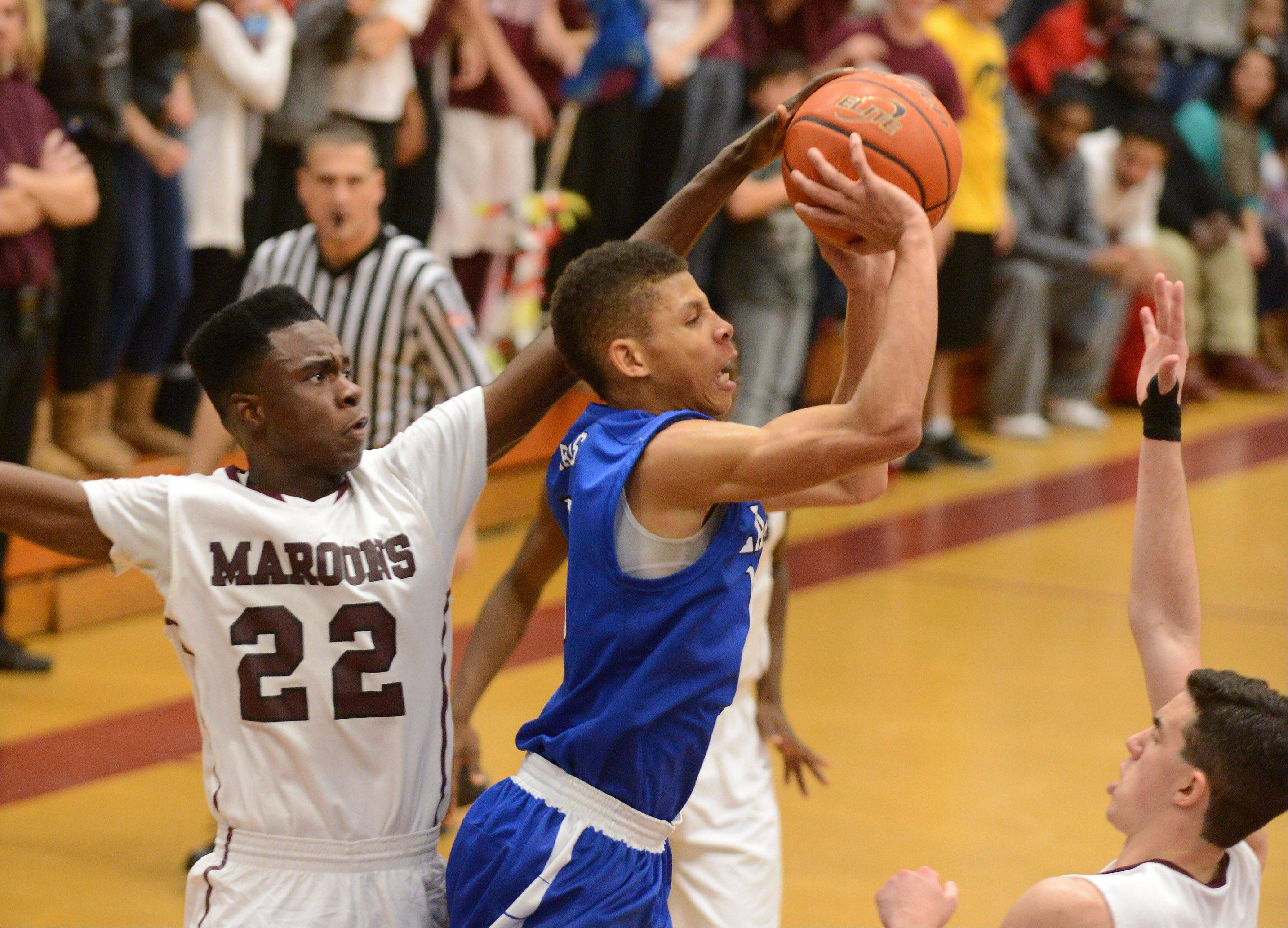 Larkin�s Kendale McCullum (10) puts up a shot between a pair of Elgin defenders, including Desmond Sanders (22), and draws a foul during Thursday�s game at Elgin.