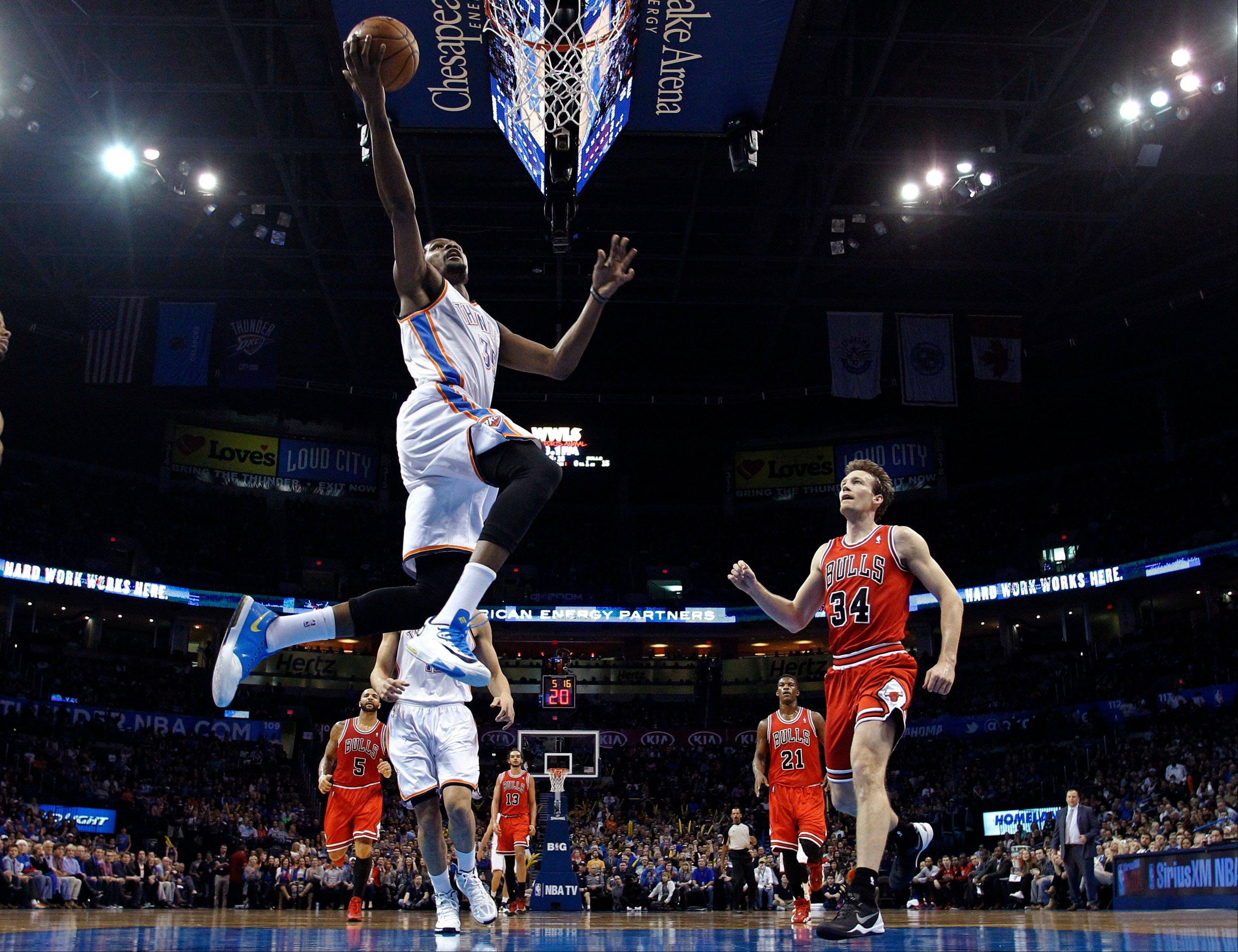 Oklahoma City Thunder forward Kevin Durant (35) shoots in front of Chicago Bulls forward Mike Dunleavy (34) during the first quarter of an NBA basketball game in Oklahoma City, Thursday, Dec. 19, 2013. (AP Photo/Sue Ogrocki)