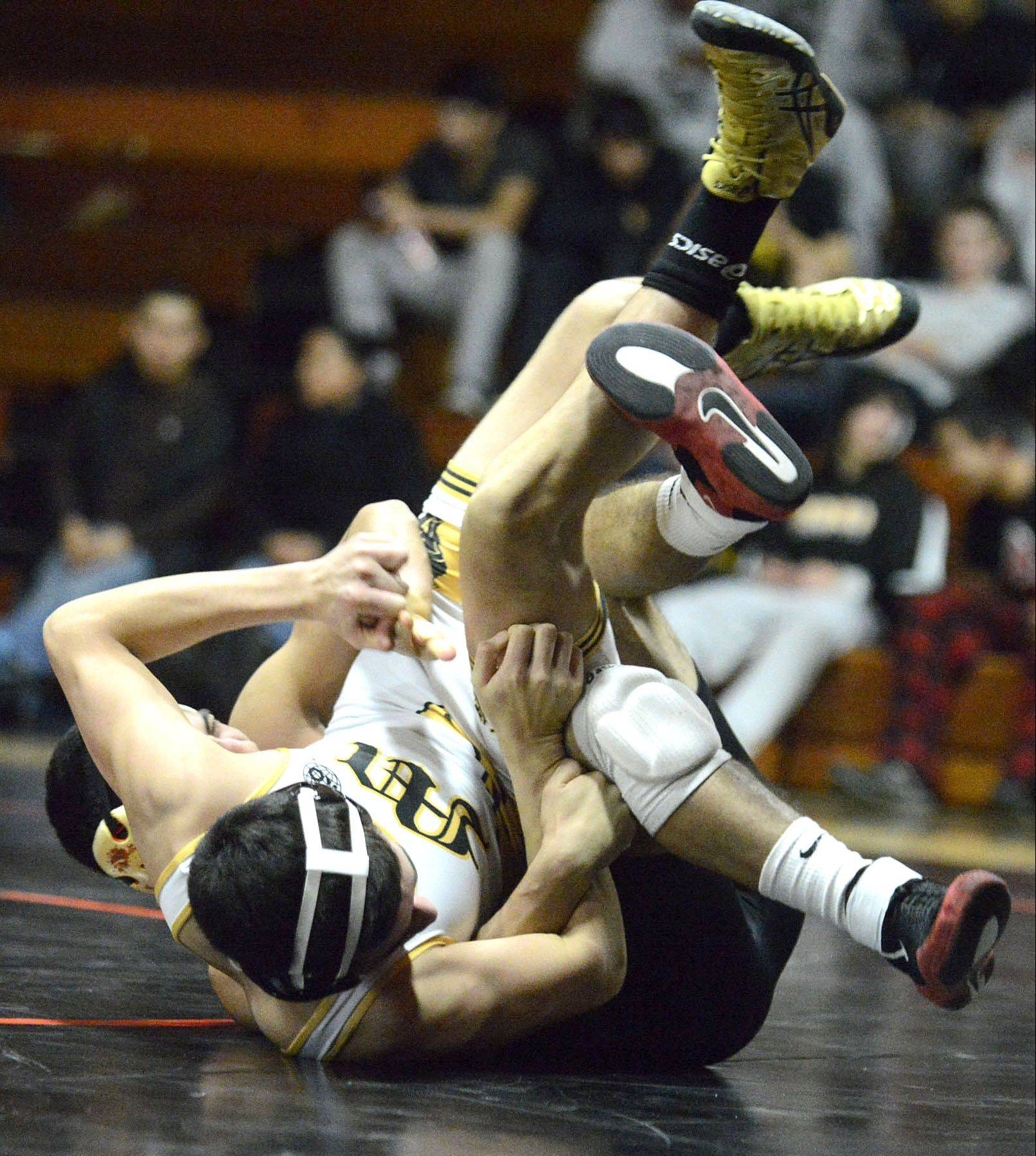 St. Charles East's Isaiah Vela flips Metea Valley's Juan Materino in their 138-pound match on Thursday. Vela won the match.