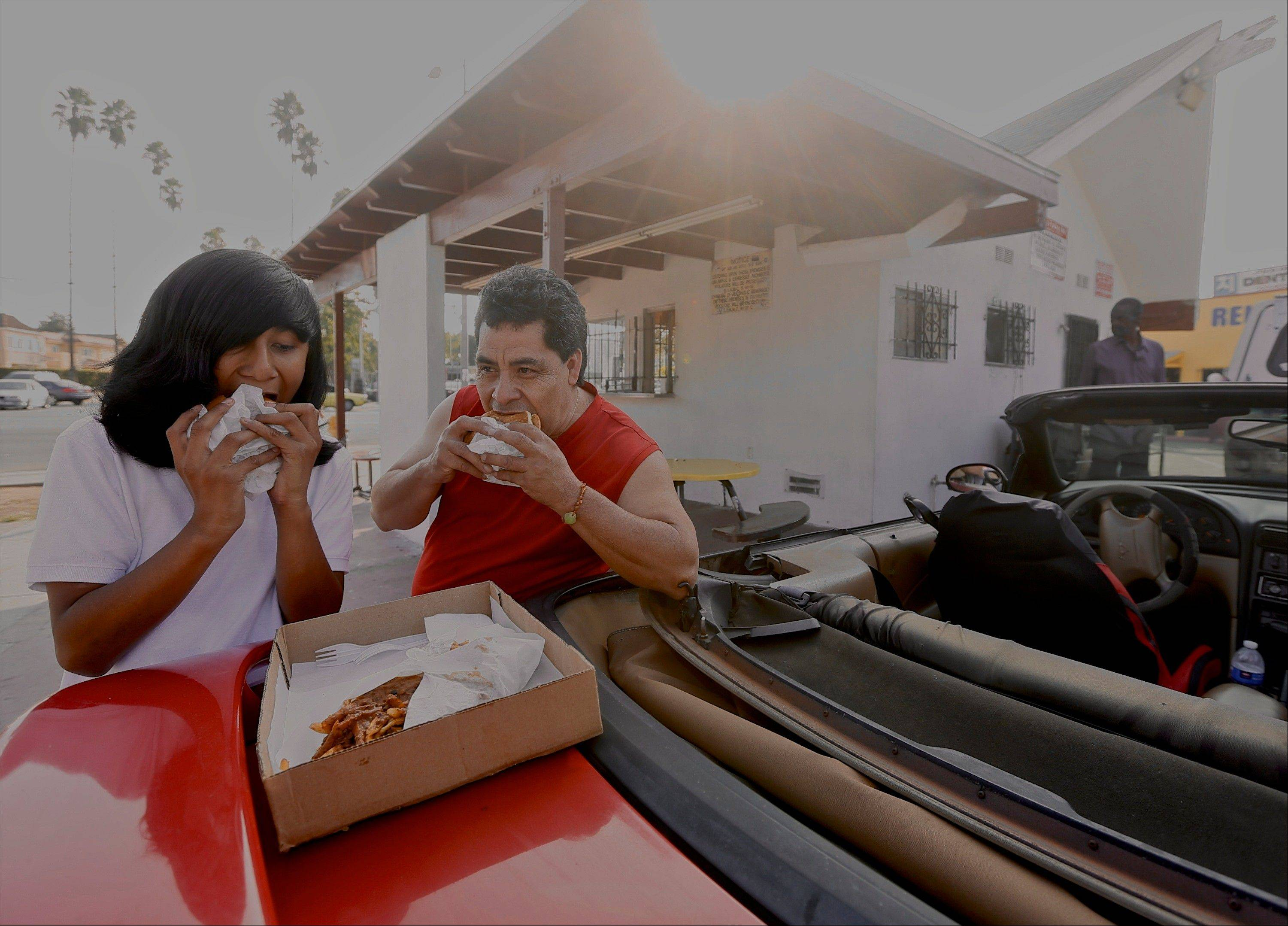 Patrons Fernando Ramos, 44, and his son Brian, 13, eat their burgers on the back of their Mustang convertible at the parking lot of Capitol Burgers in Los Angeles.
