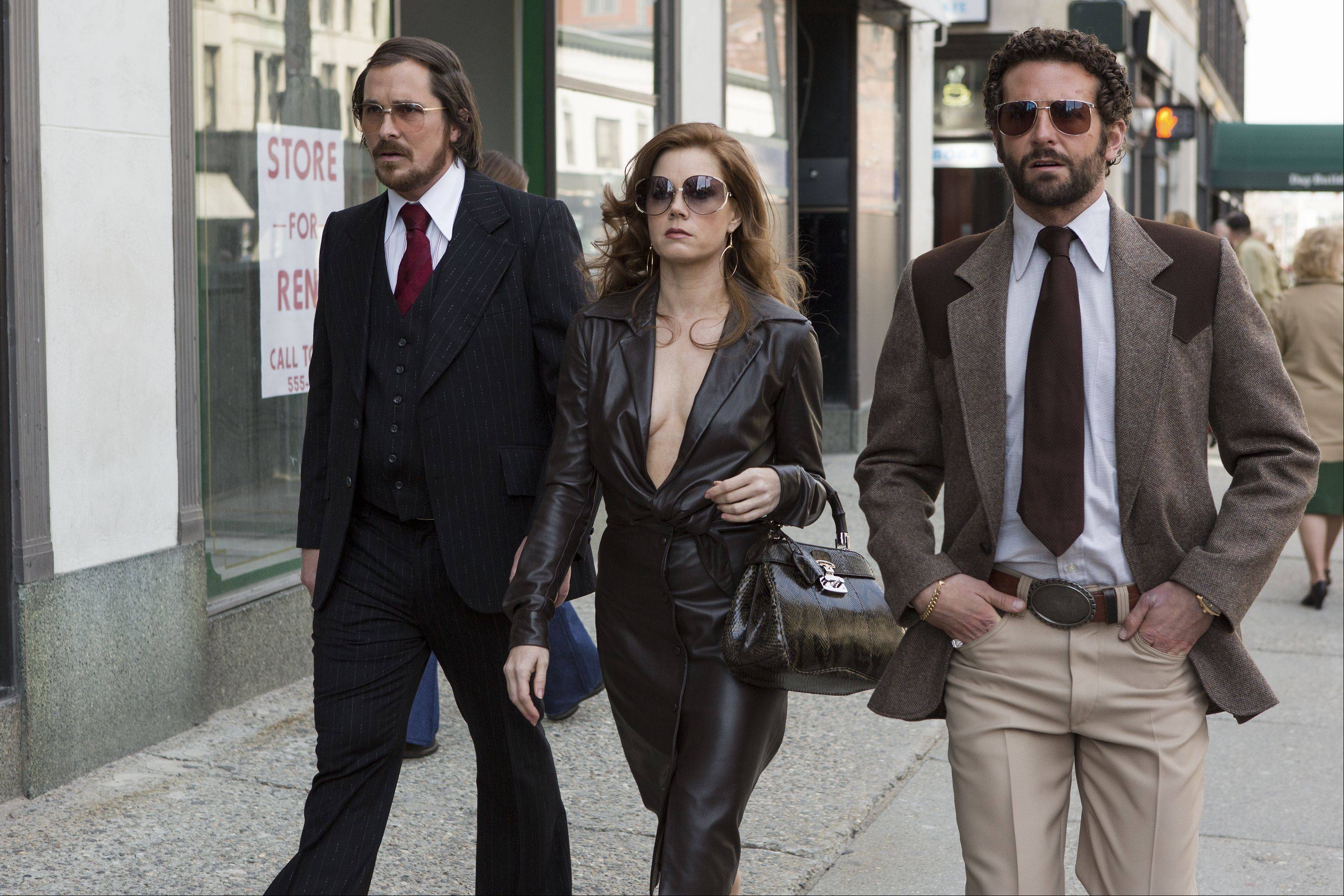 "Con man Irving Rosenfeld (Christian Bale), left, Sydney Prosser (Amy Adams) and federal agent Richie DiMaso (Bradley Cooper) set up a corruption sting in ""American Hustle."""