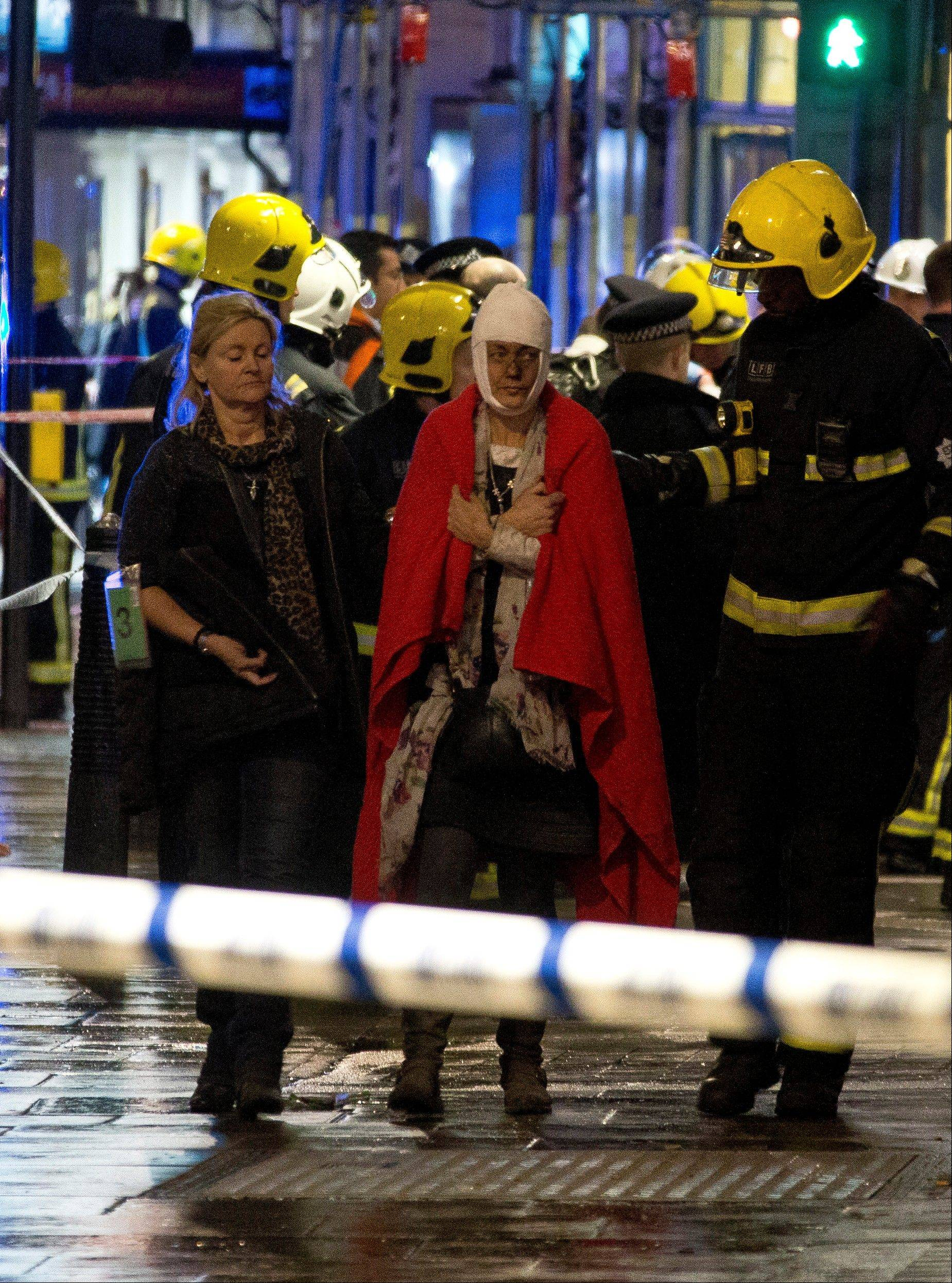 A woman walks, bandaged and wearing a blanket given by emergency services, after a theater in London partially collapsed Thursday evening.