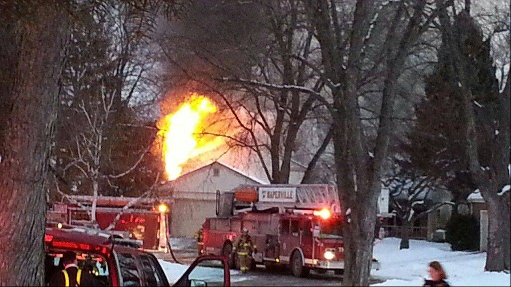 A fire blazes Wednesday morning at the home of Tom and Jan Lambert on the 1200 block of Field Court in Naperville.