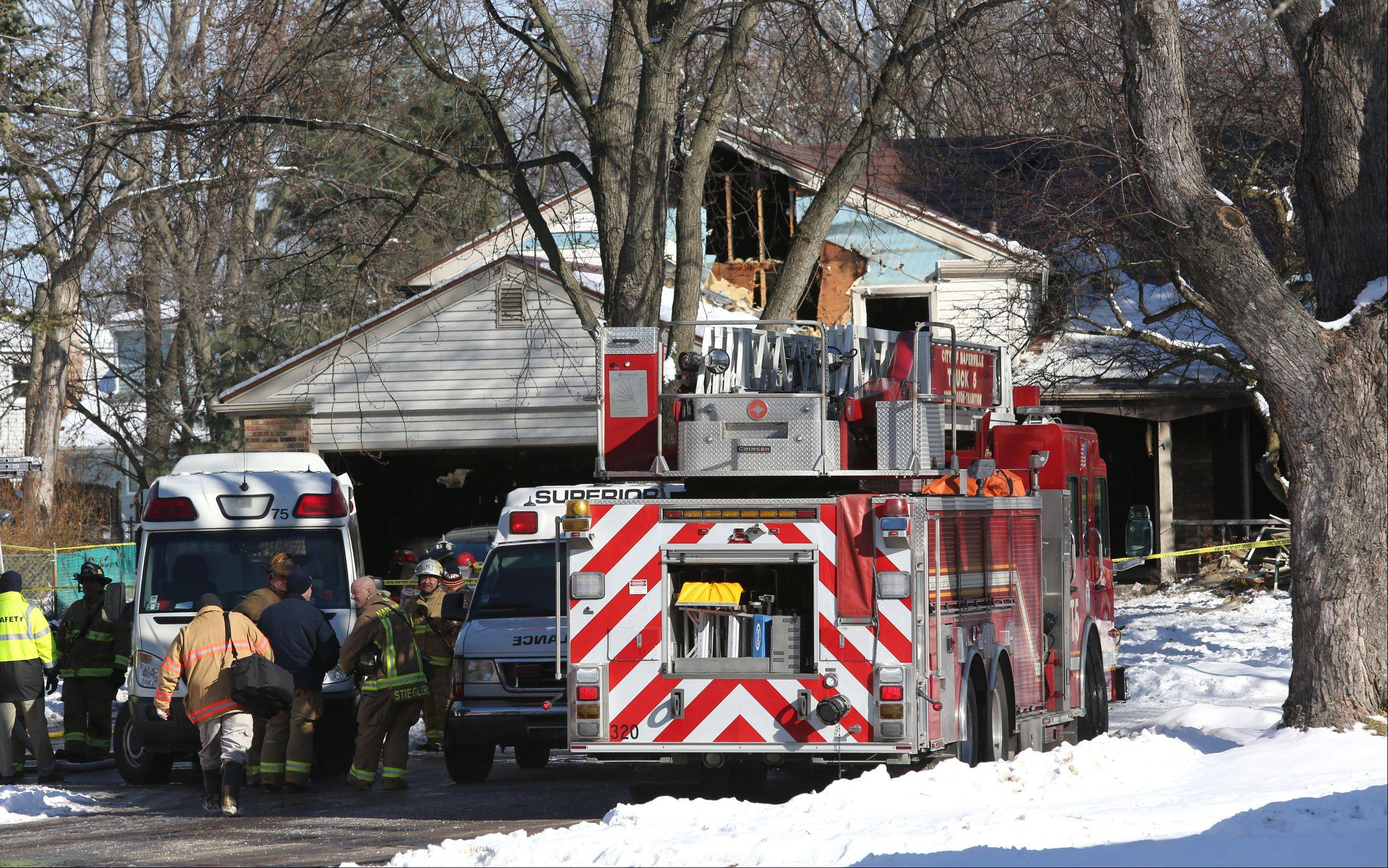 Ambulances prepare to remove the bodies of two people killed in a morning house fire Wednesday on the 1200 block of Field Court in Naperville.