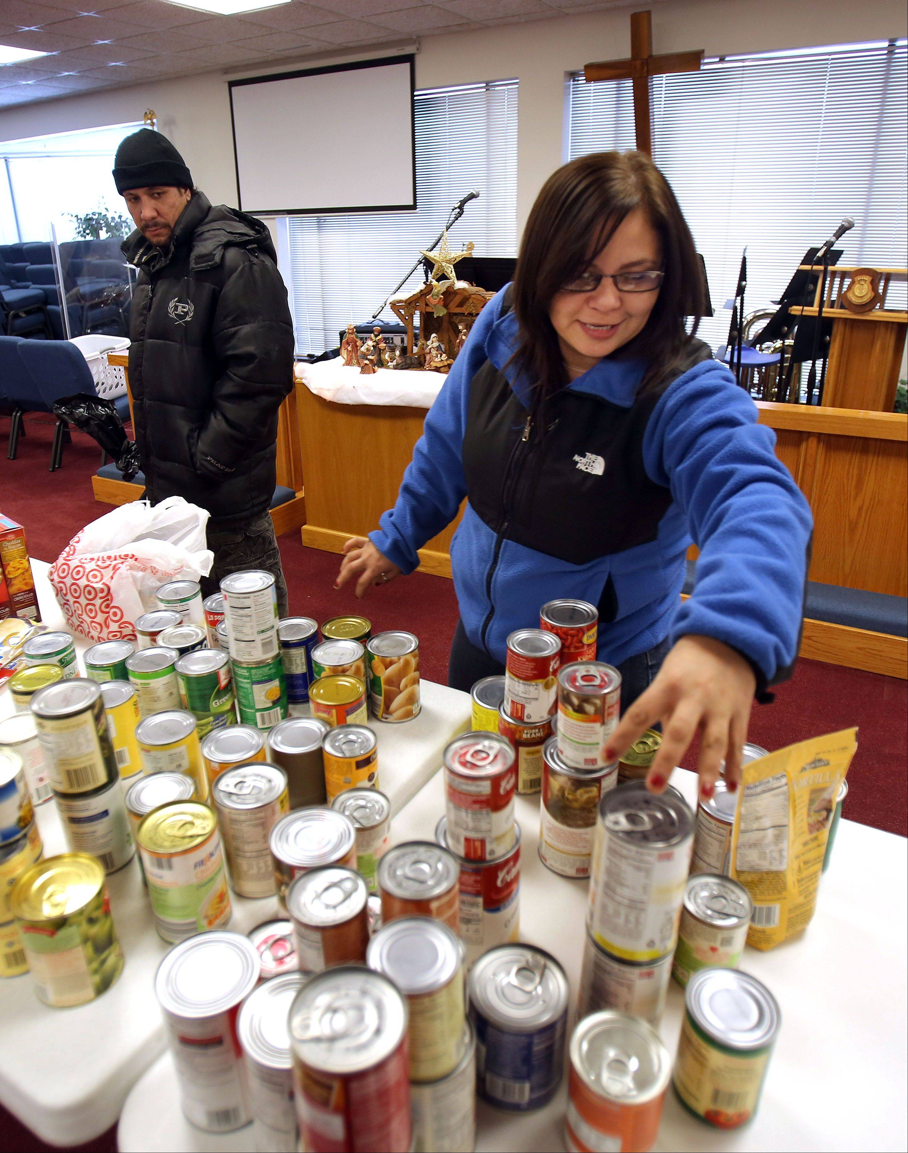 Waukegan residents Beatrice Ocegueda, right, and her husband, Cesar, sort through nonperishable food items during the Angel Tree program on Thursday at the Salvation Army Waukegan Corps Community Center. The food was donated by the Gurnee Police Department.