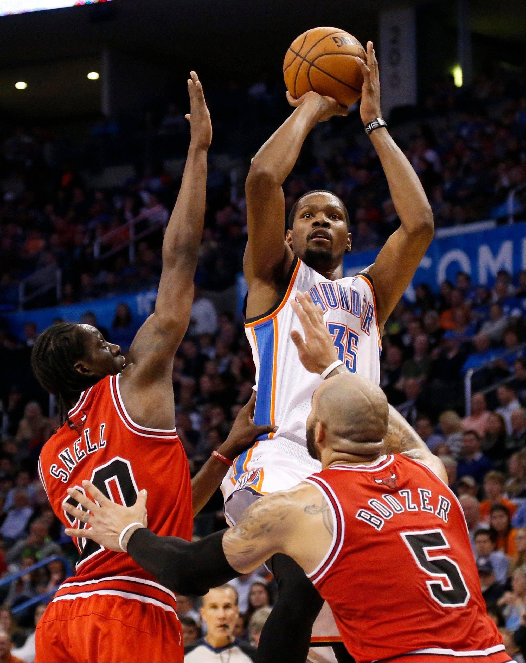 Oklahoma City Thunder forward Kevin Durant (35) shoots over Chicago Bulls forwards Tony Snell (20) and Carlos Boozer (5) during the fourth quarter of an NBA basketball game in Oklahoma City, Thursday, Dec. 19, 2013. Oklahoma City won 107-95.