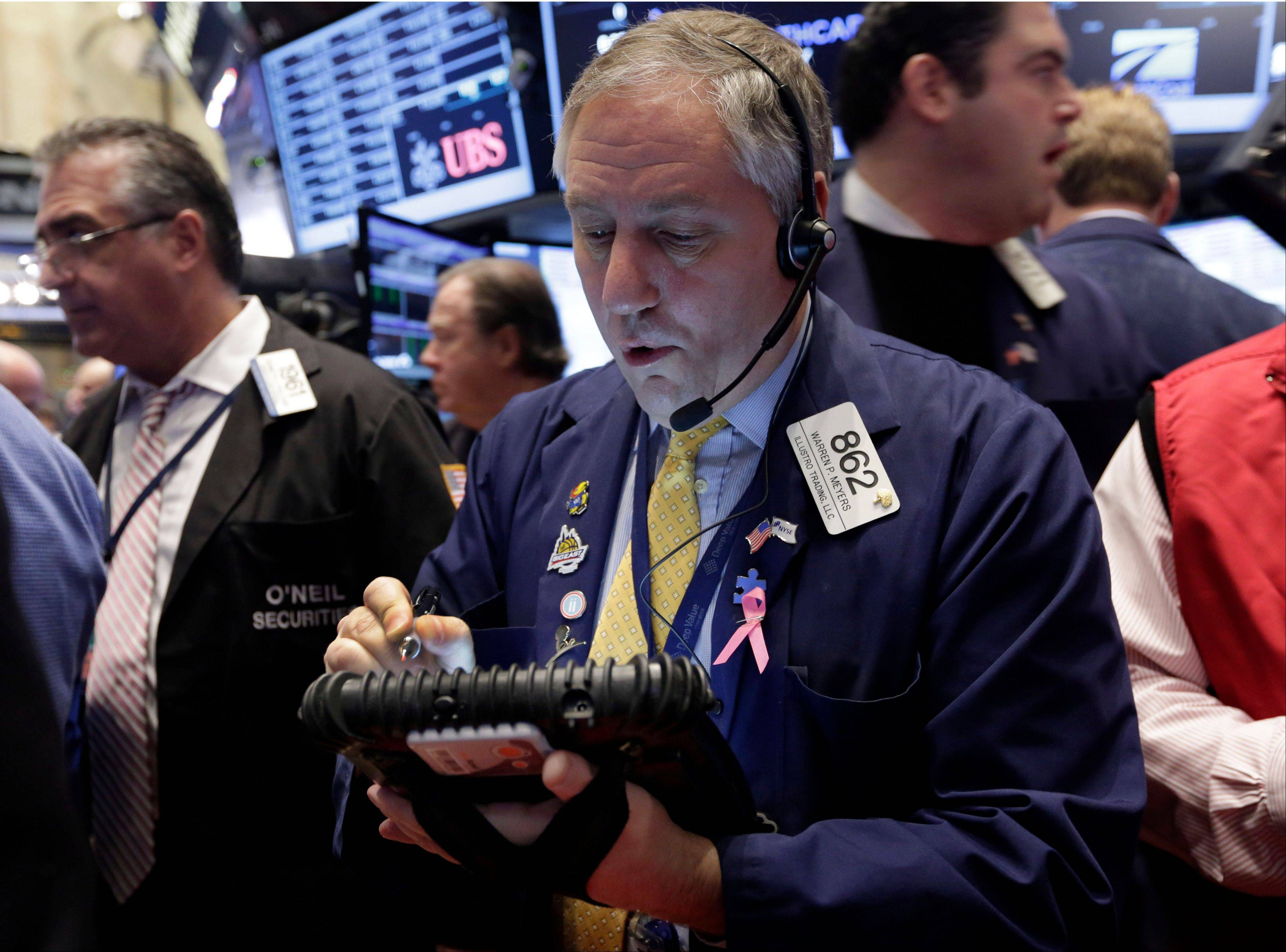 Trader Warren Meyers, center, works Wednesday on the floor of the New York Stock Exchange. Investors continued Friday to breathe a sigh of relief that the U.S. central bank has committed to keeping interest rates low.