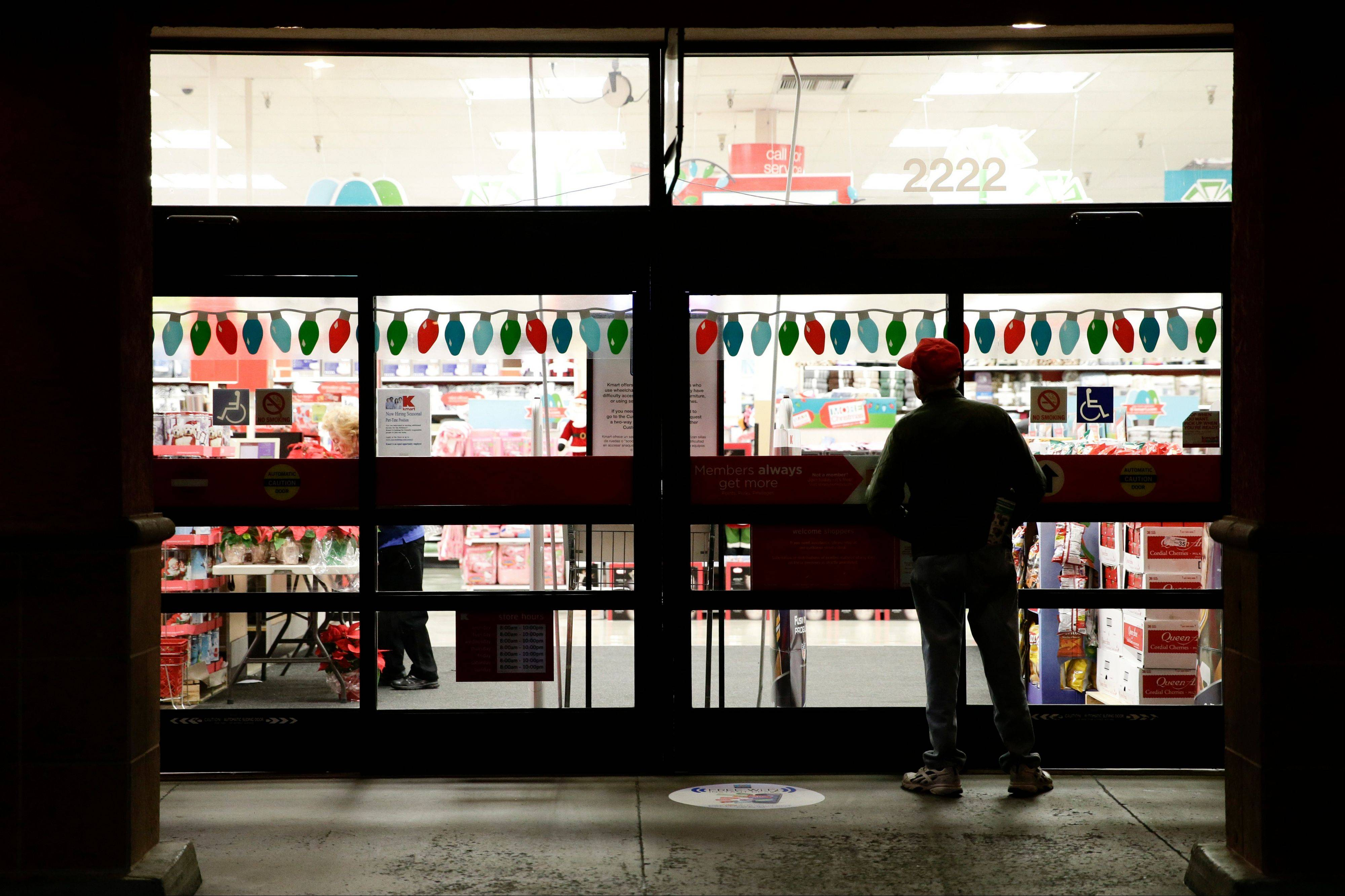 A shopper waits outside a Kmart store for it to open in Anaheim, Calif.