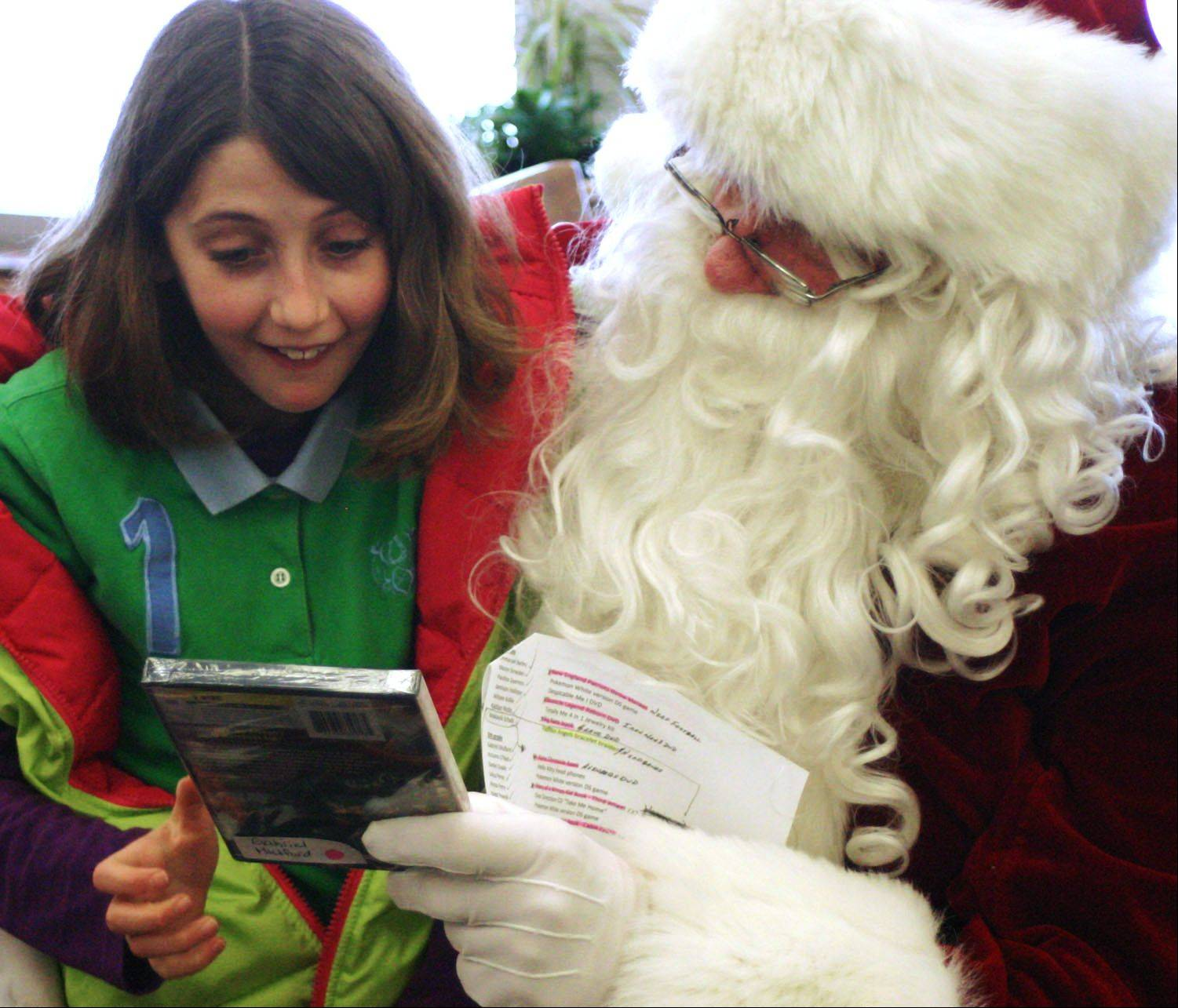 Mooseheart fifth-grade student Gabriele Mulford�s eyes lit up when she received a DVD from Santa Claus Thursday.