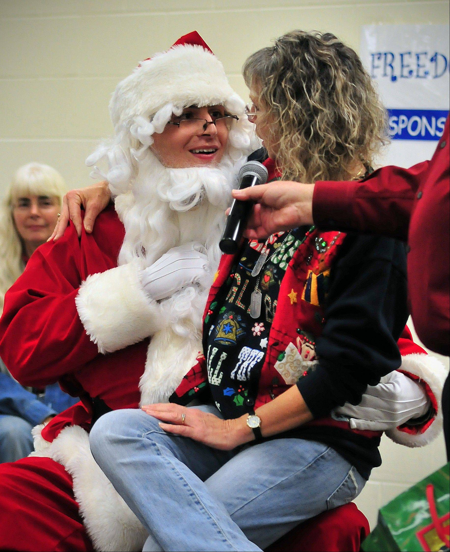 Army Spc. Ethan Harris, masquerading as Santa Claus, gives his mother, Kim Harris, a high school math teacher, quite the Christmas present Friday in Brushy Prairie, Ind., by coming home early from a tour in Afghanistan.