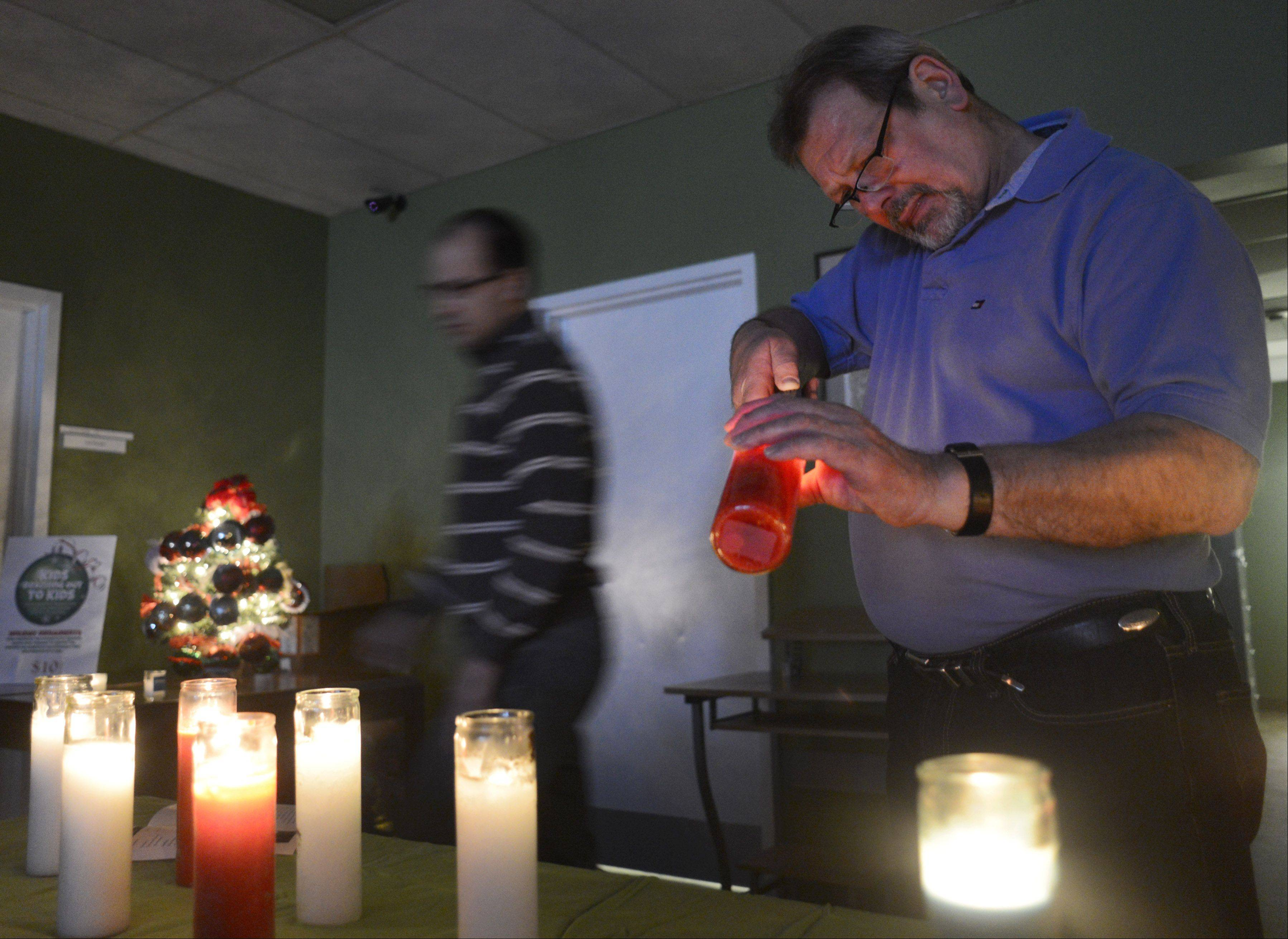 Case manager John Aliprandi, right, and Clinical Director Todd Stull light candles as Journeys-The Road Home in Palatine holds its annual Homeless Memorial Service to honor the area's homeless who have died during the past year.