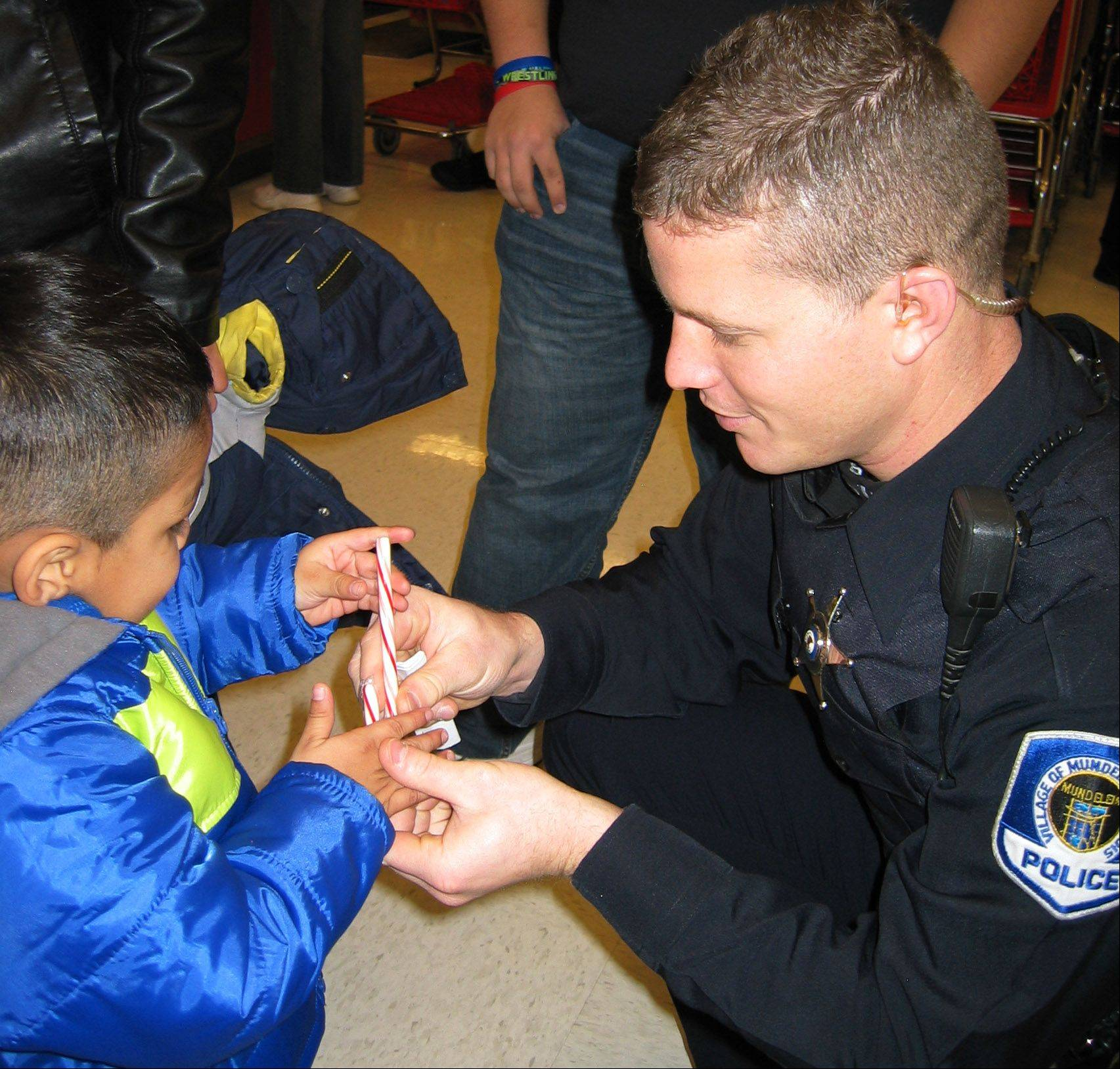 Mundelein Police Officer Rick Witt shares a special moment with one of the children who participated in the village of Mundelein´s Shop With A Cop program.