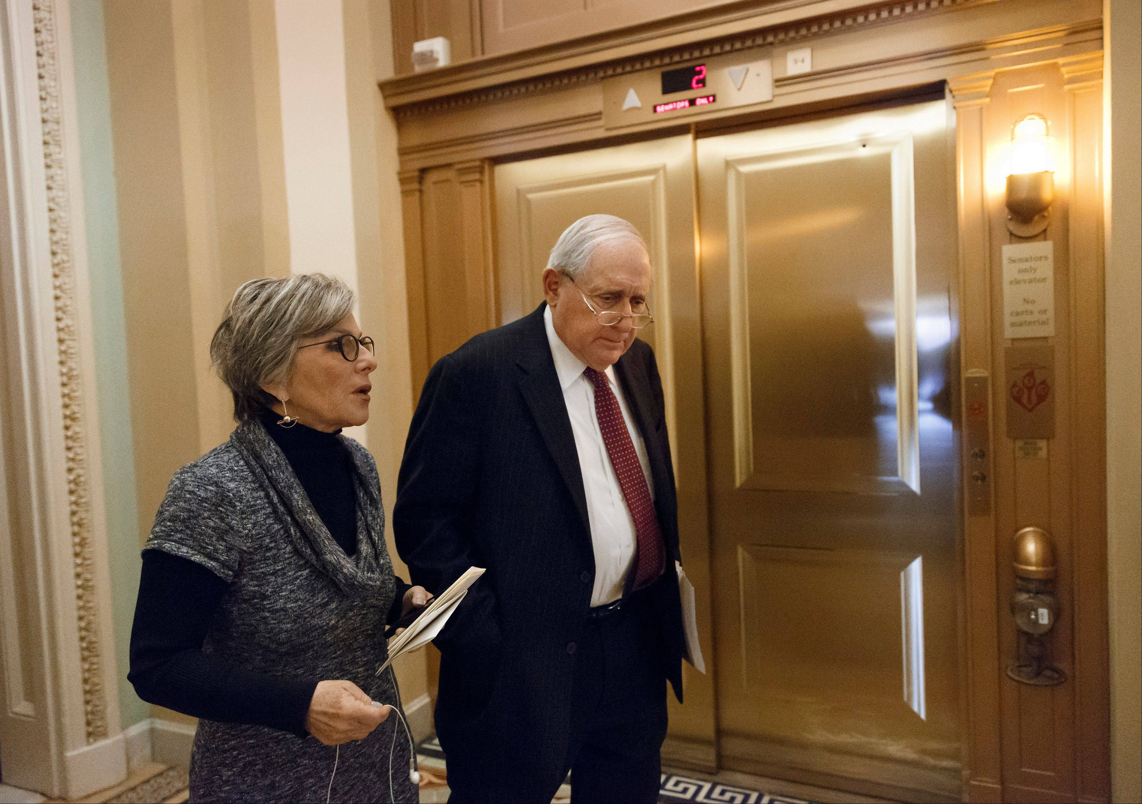 Senate Armed Services Committee Chairman Carl Levin, D-Mich., right, confers with Sen. Barbara Boxer, D-Calif., as a vote nears on a sweeping, $633 billion defense bill, at the Capitol in Washington, Thursday, Dec. 19, 2013.