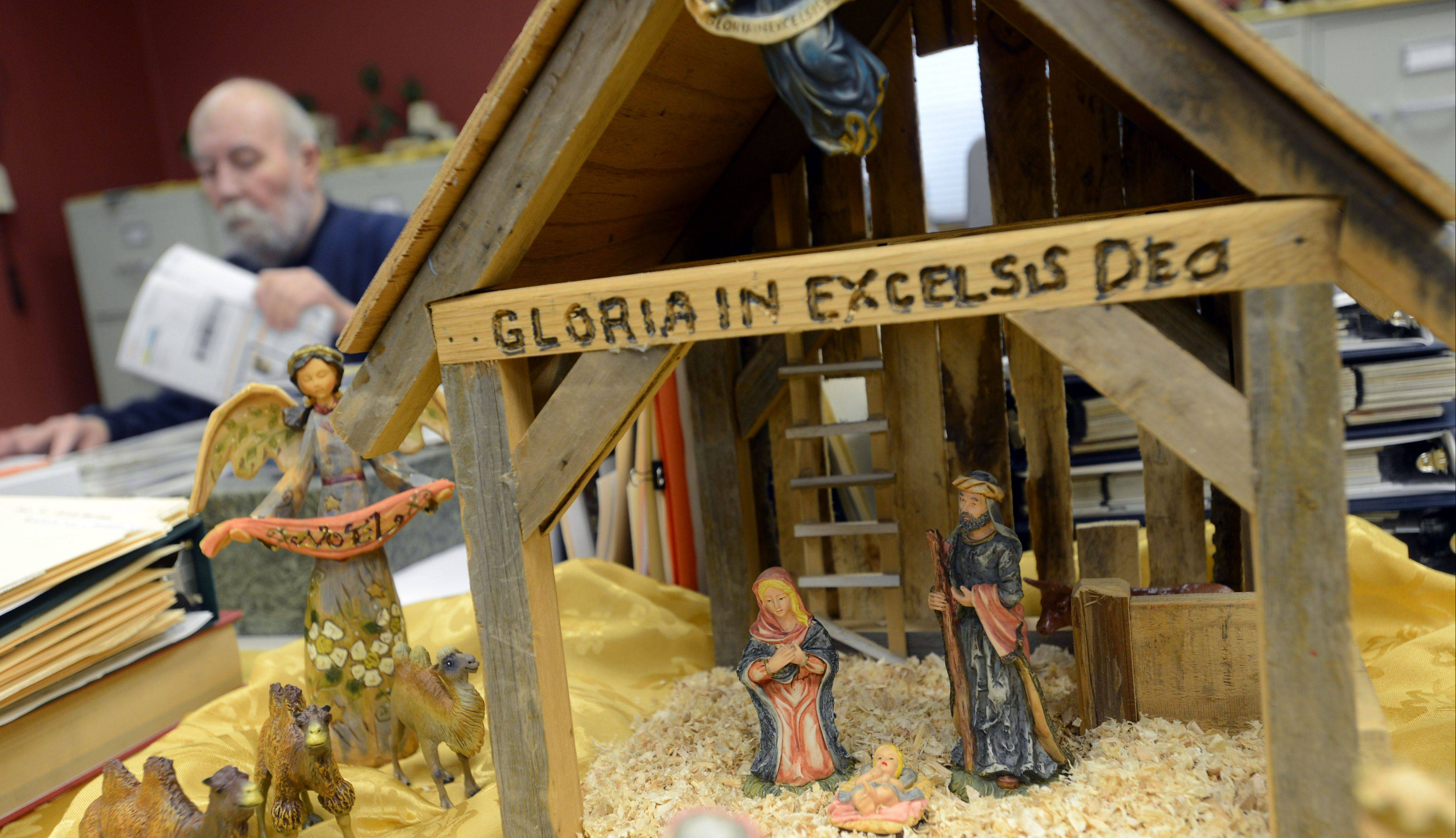 Ela Historical Society and Museum President Ron Frank works near one of the Nativity sets on display in Lake Zurich.