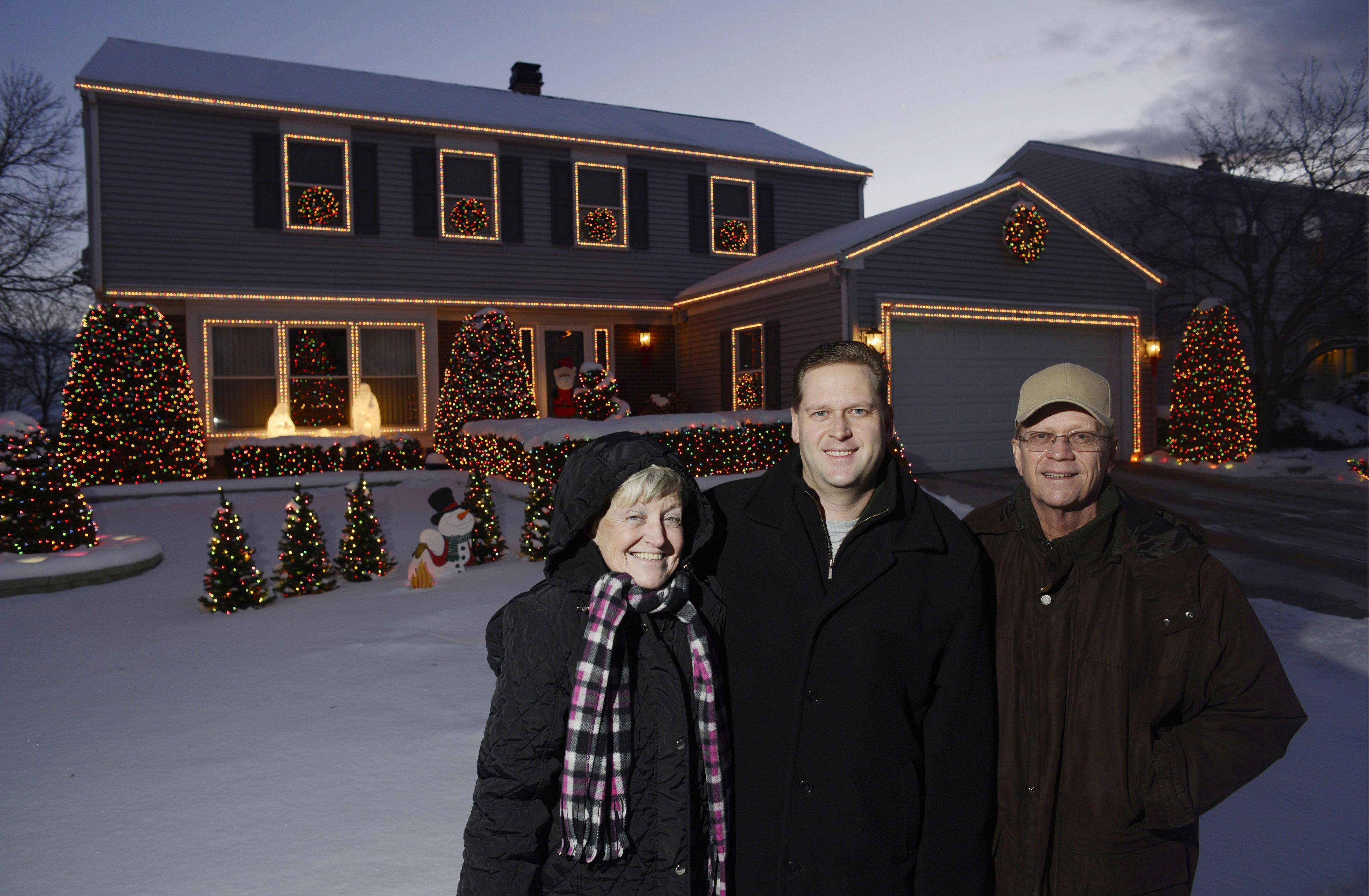 Todd Mickley stands with his parents, Donna and Hank, in front of their Schaumburg home, which has been decorated with 18,000 holiday lights, at 2049 Tiffany Drive. The Mickleys won the Editor's Choice award for the Northwest suburbs in the Daily Herald's holiday lights contest.
