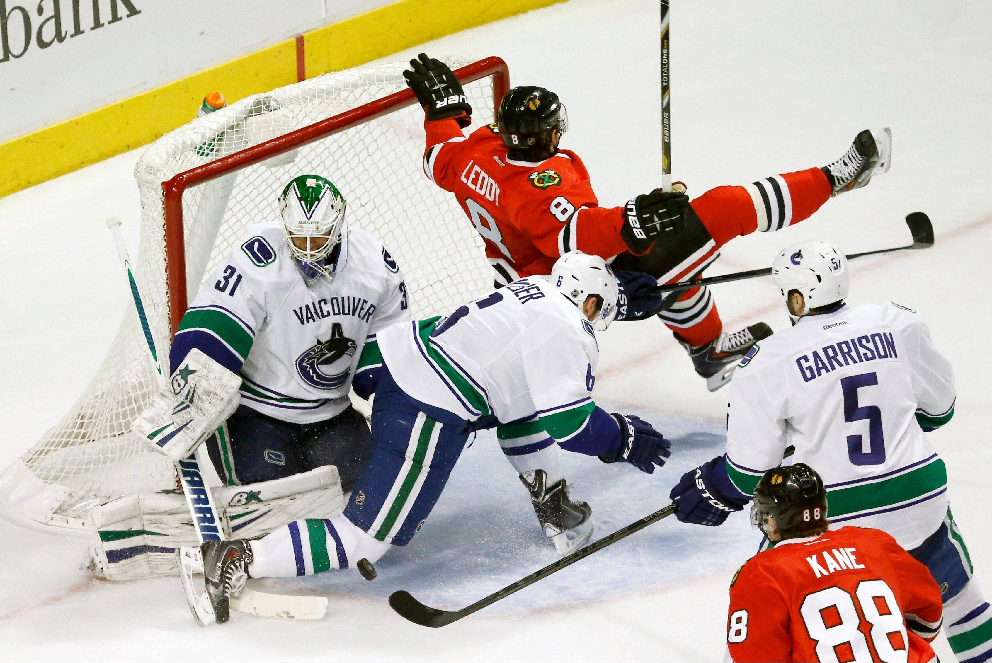 Despite chaos all around him, rookie Canucks goalie Eddie Lack makes a save against the Blackhawks on Friday at the United Center.