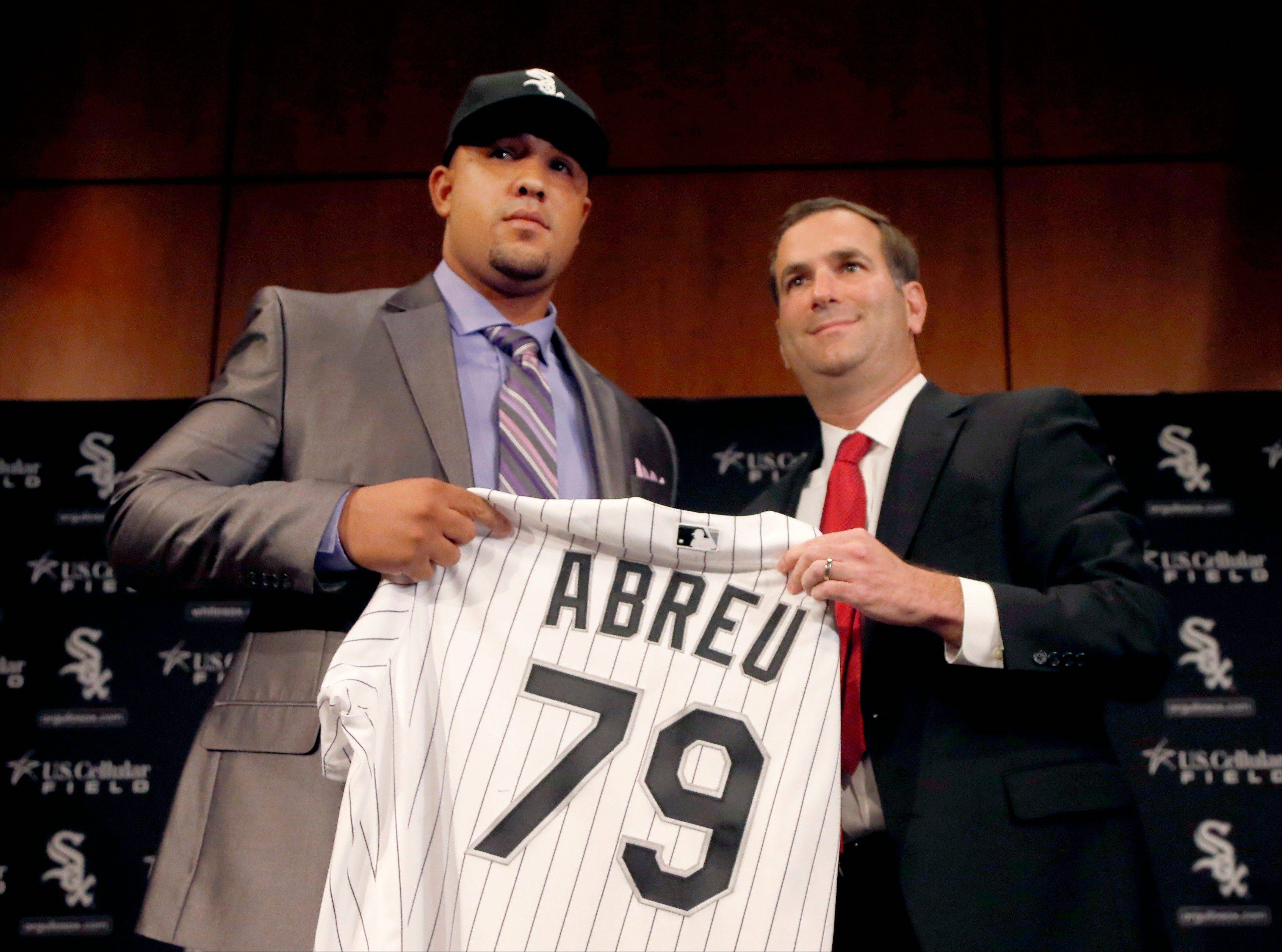 Cuban slugger Jose Abreu, left, smiles with Chicago White Sox General Manager Rick Hahn during a news conference where Hahn announced a six-year, $68 million deal with Abreu. Mike Spellman likes all of Hahn's moves so far though he was sad to see Jose Santiago go.