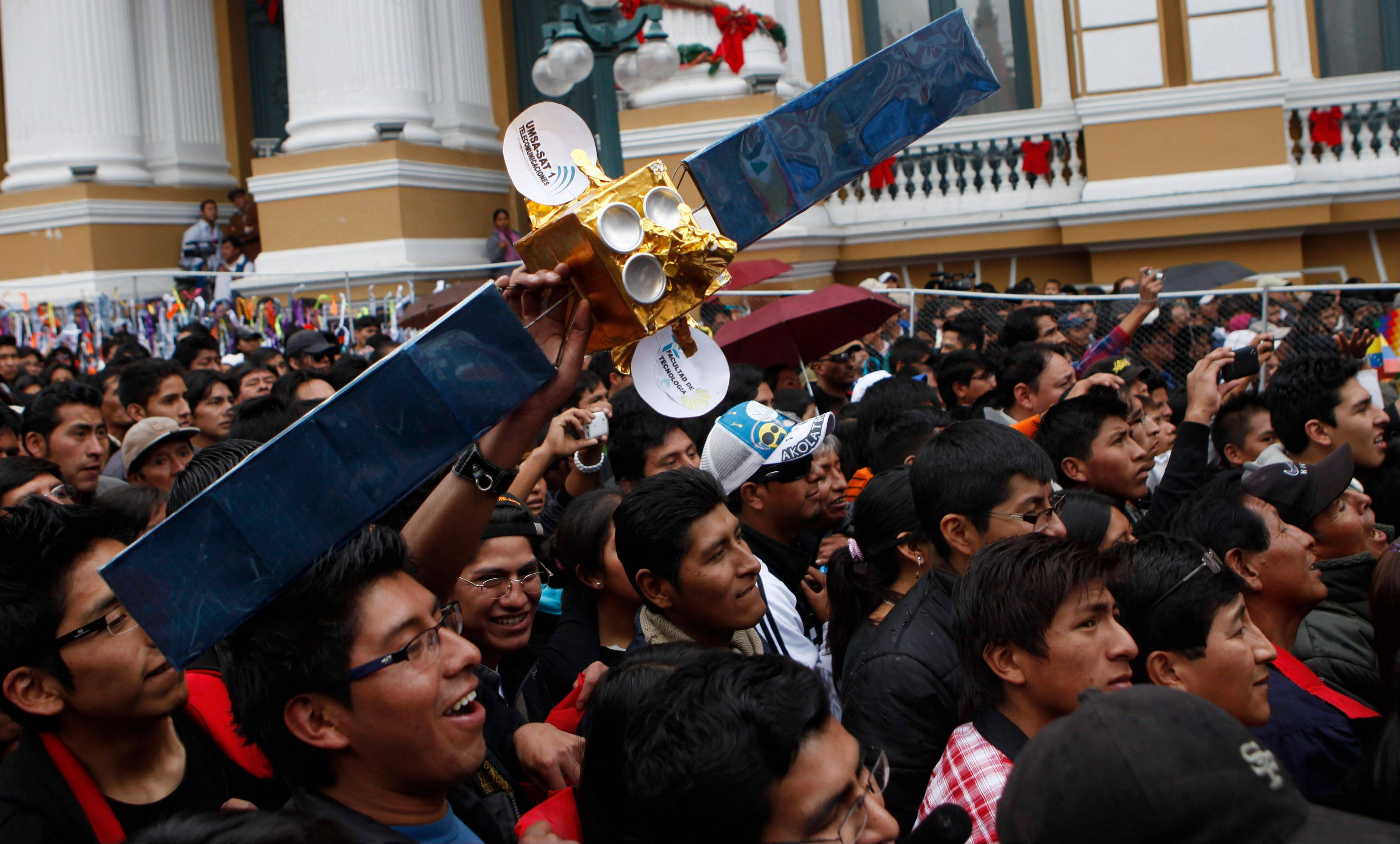 A man in La Paz holds a miniature replica of the Bolivia's first telecommunications satellite during the live broadcast Friday from China of the launch.