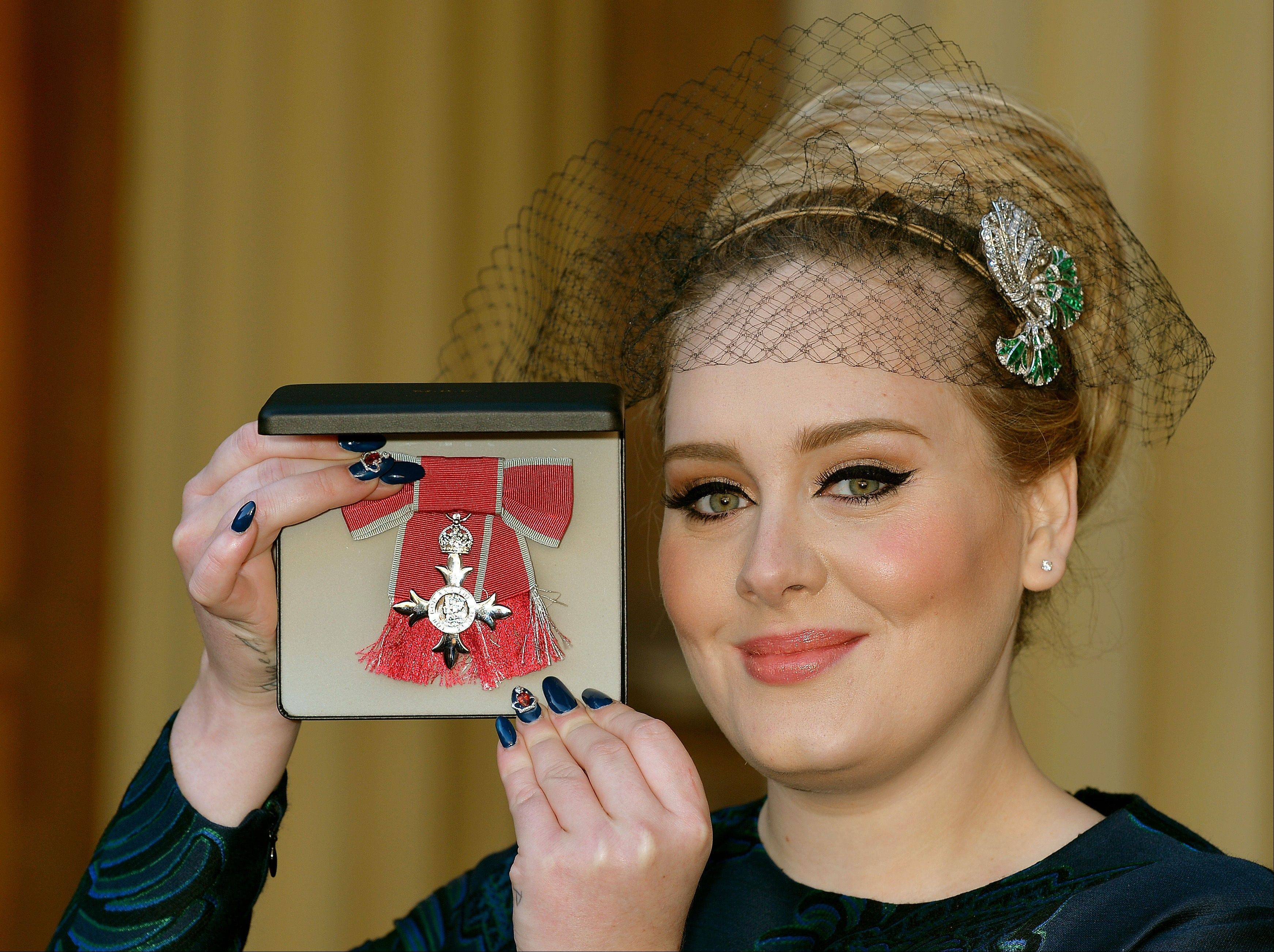 British singer Adele Adkins holds her MBE for services to music presented to her by the Prince of Wales at Buckingham Palace in London, Thursday, Dec. 19, 2013.